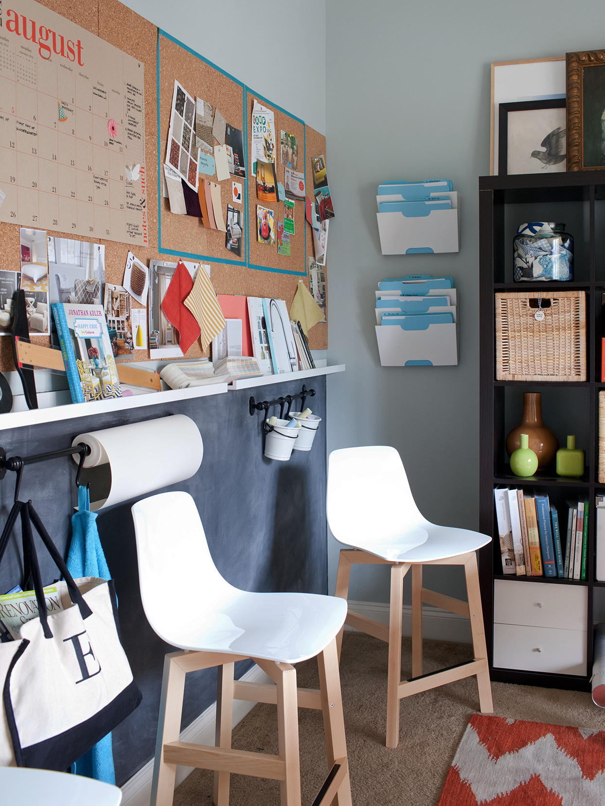 home office with cork board wall and white mod chairs