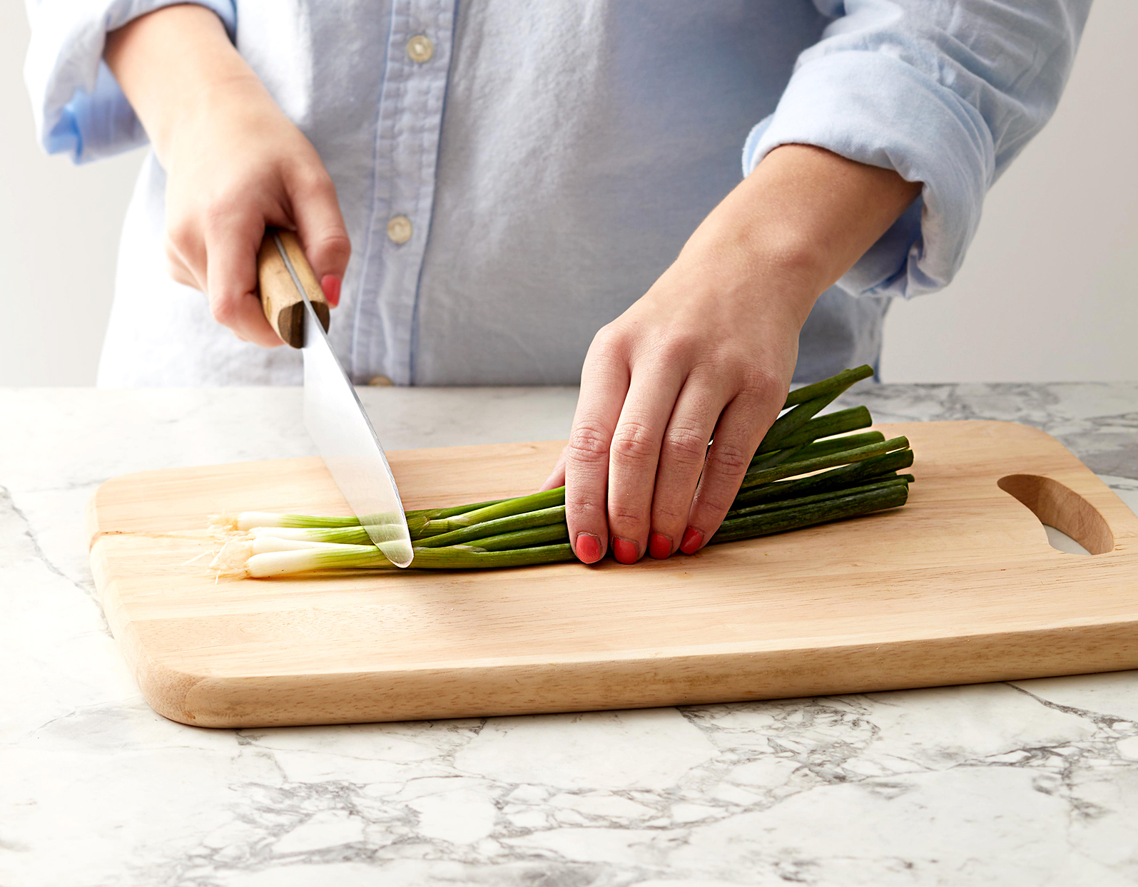 Person cutting green onion ends
