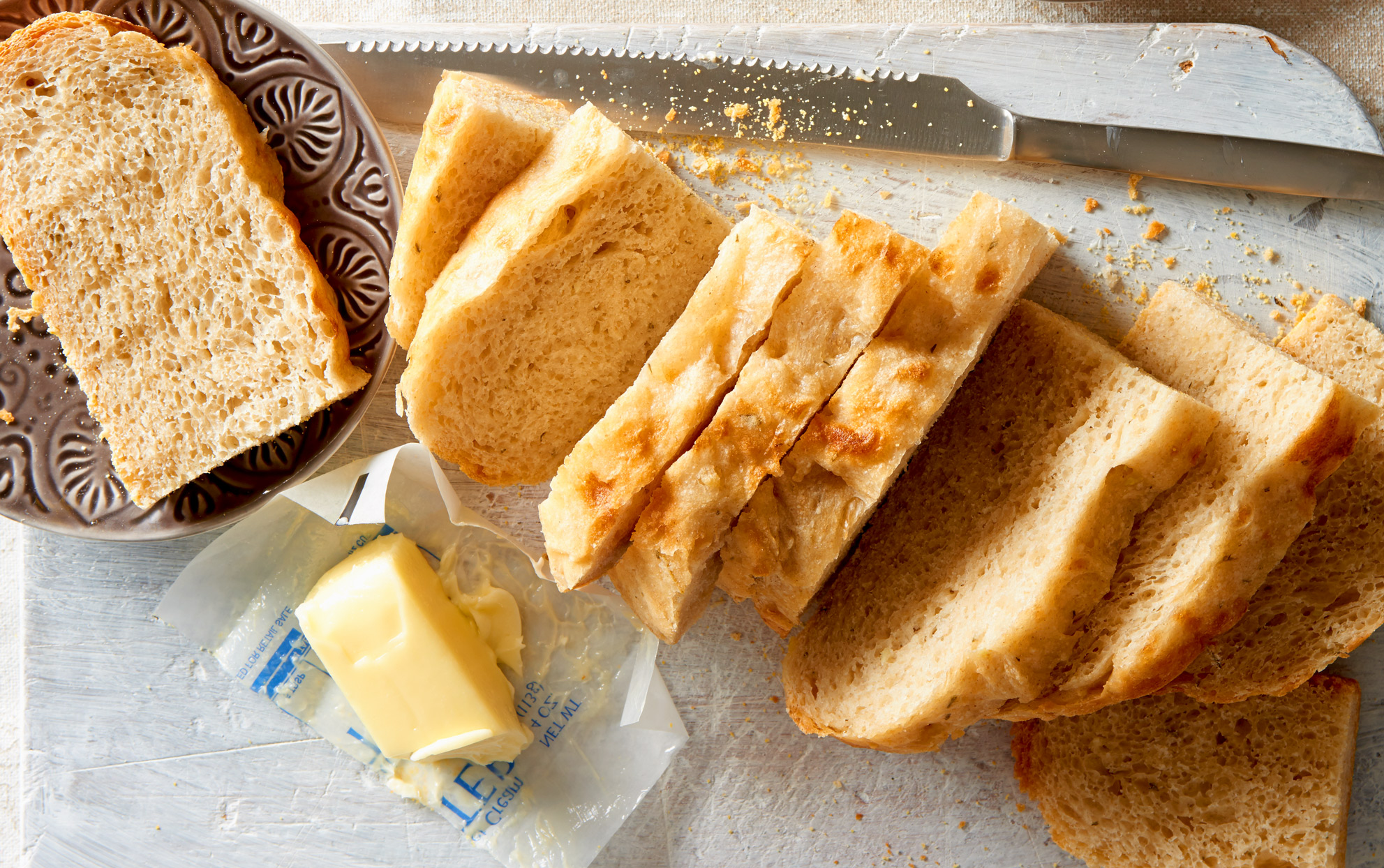 overhead view of homemade sliced bread with butter