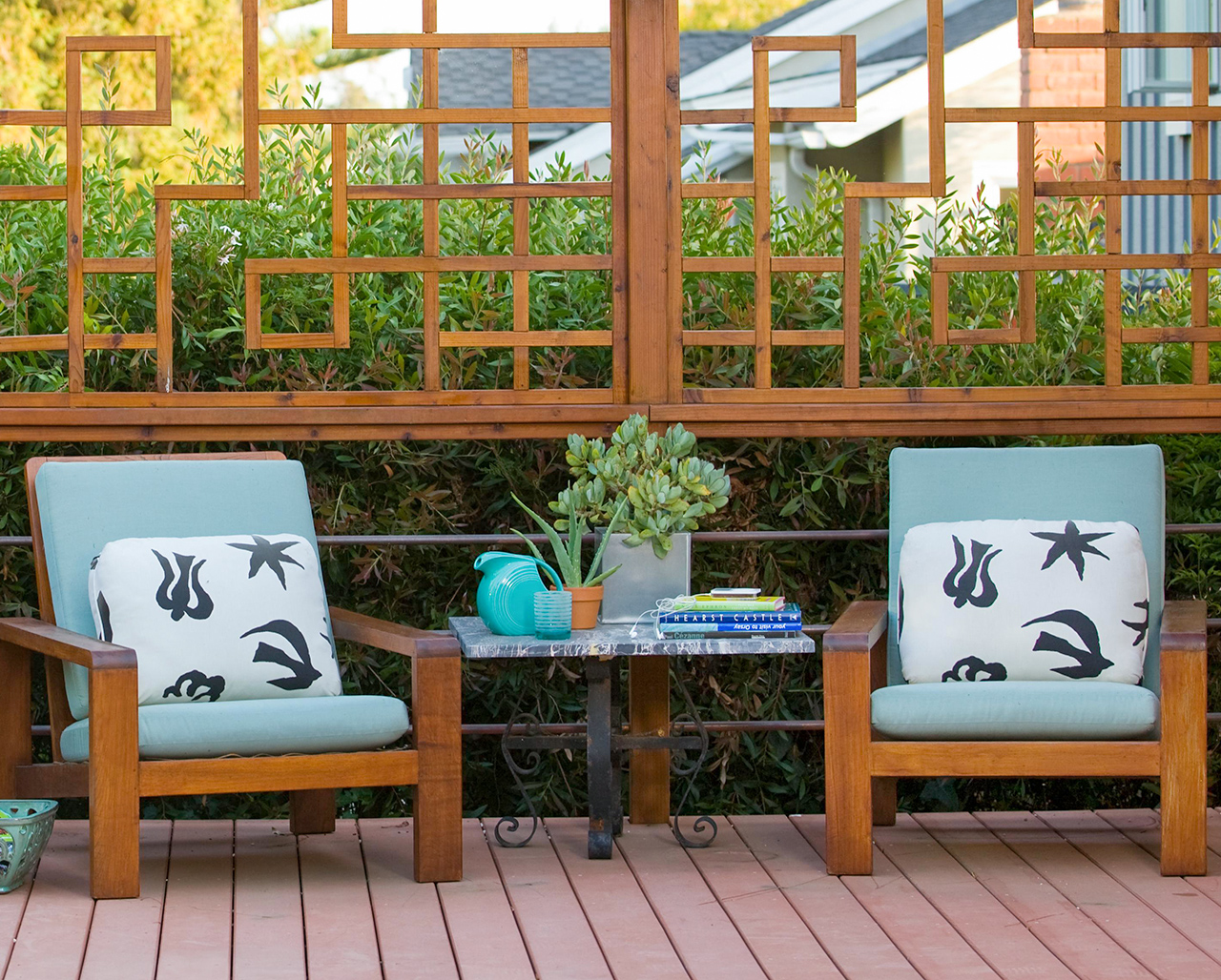 two light-blue cushioned chairs in front of upper railing wood design on deck