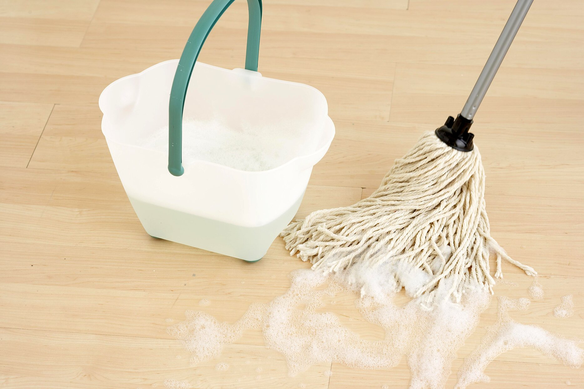 Mopping with a string mop and bucket of soap and water