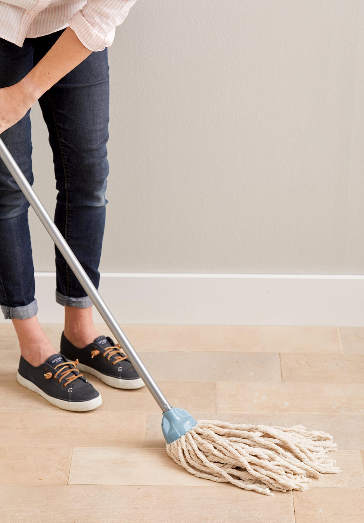 Person mopping floor with string mop