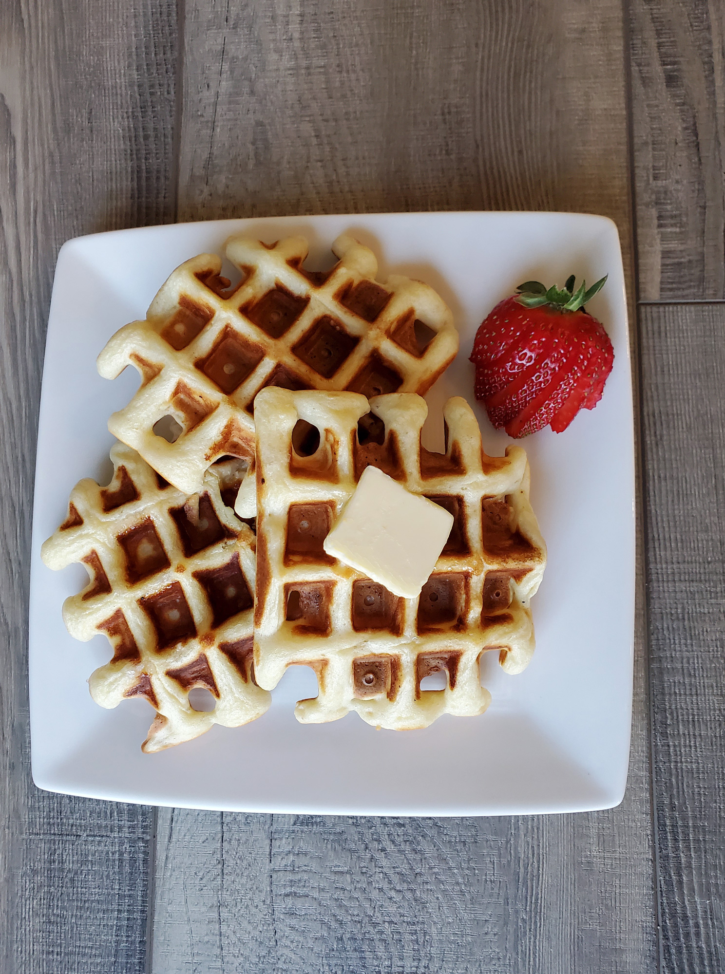 plate of overnight waffles with butter