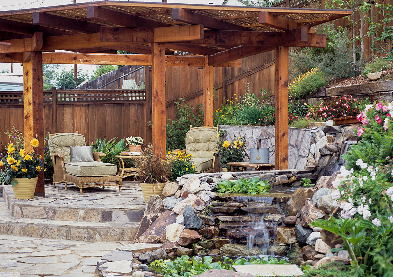 flagstone patio sitting area with garden stream