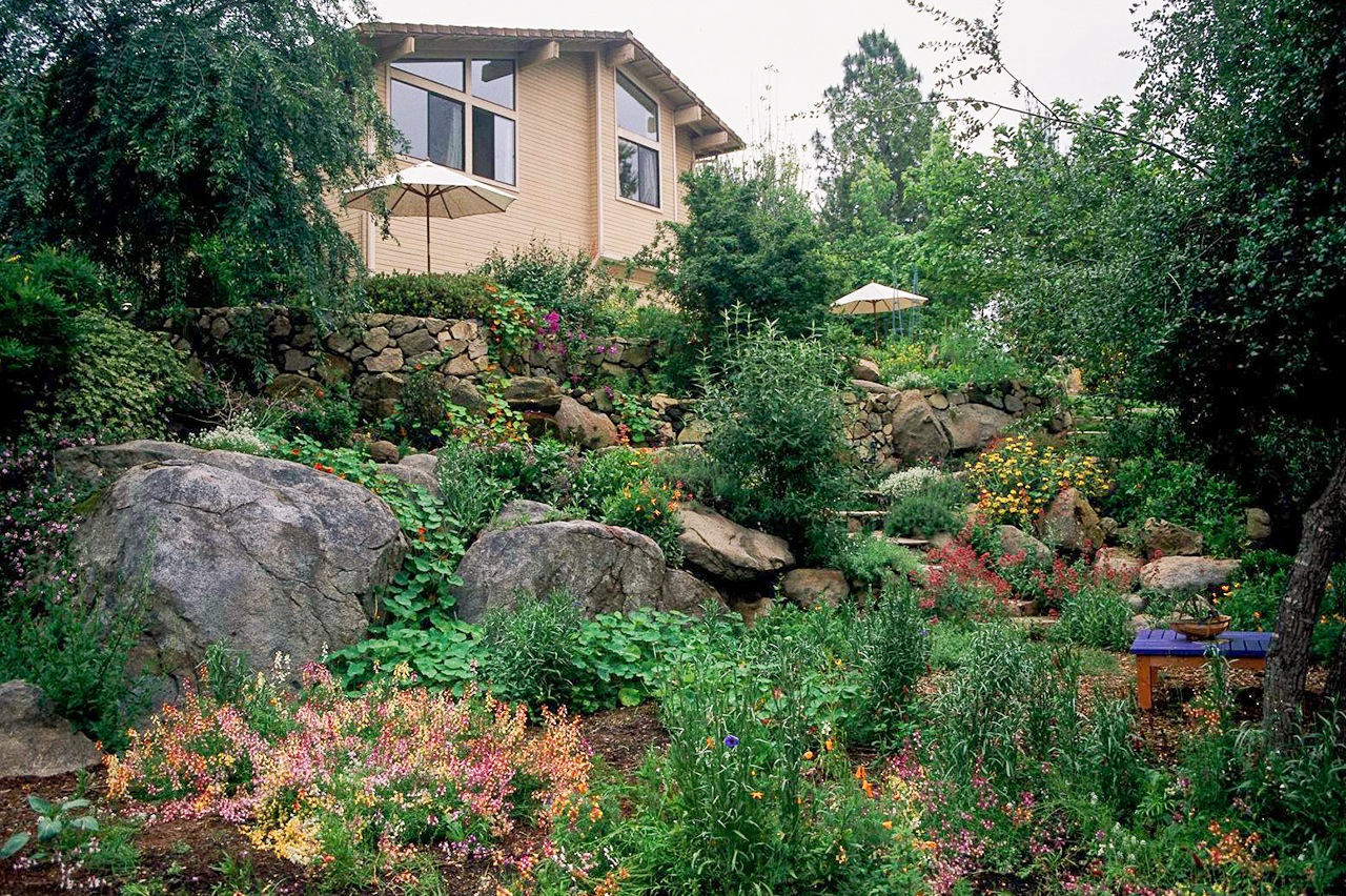 garden slope with rock layers steps to house