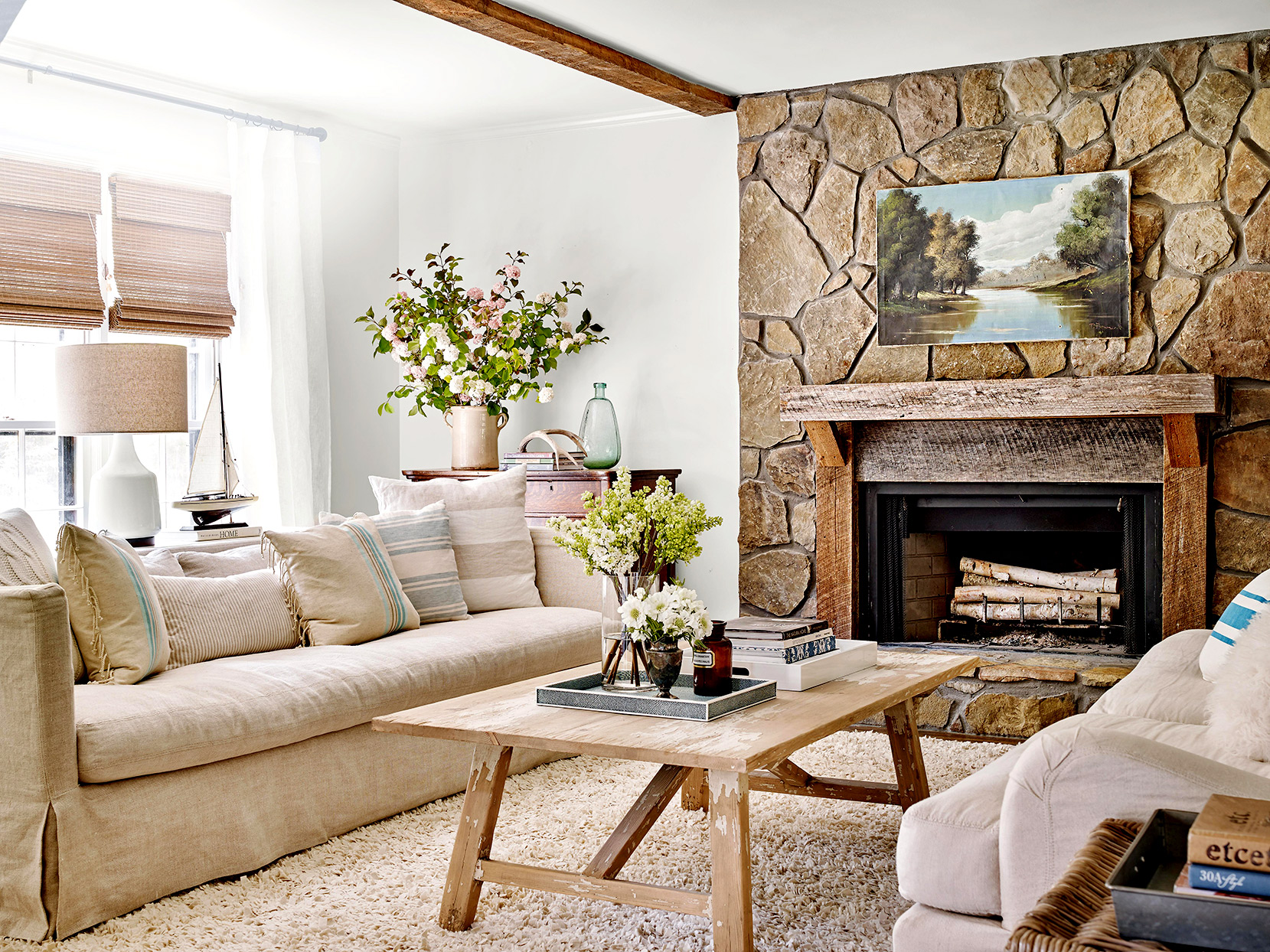 Living room with stone fireplace and white couches