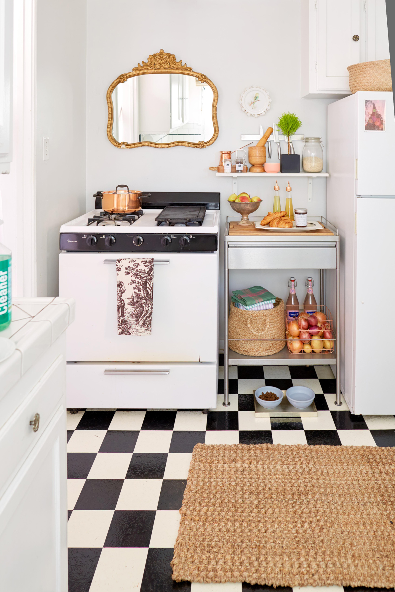 Small white kitchen black and white checked floor with rattan rug
