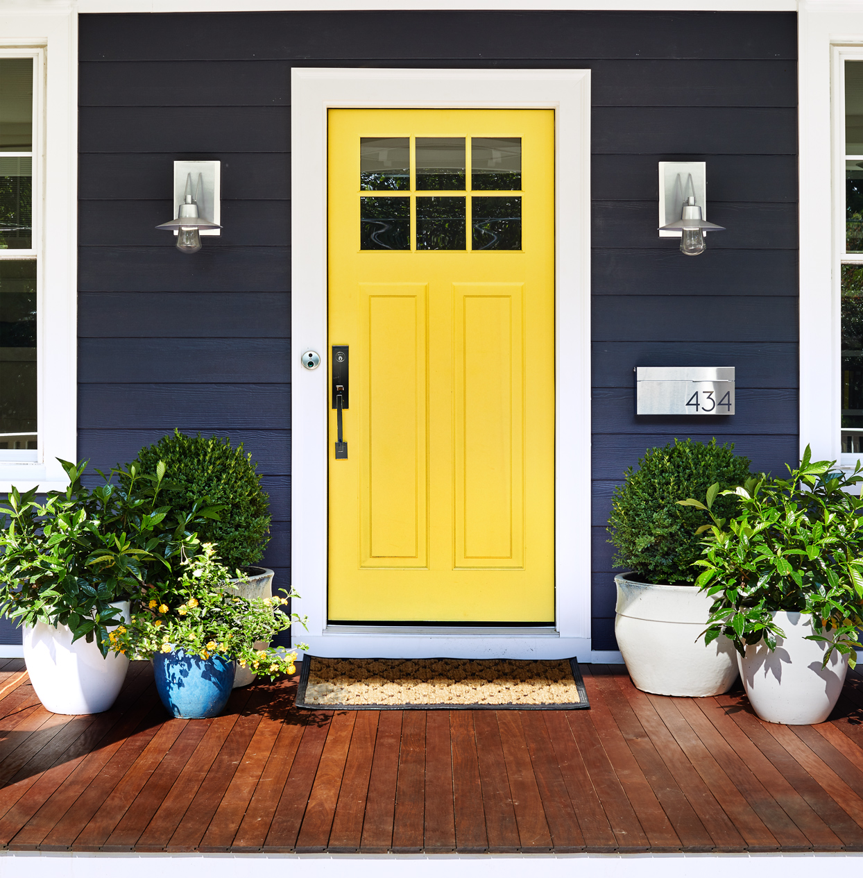 yellow front door large potted plants