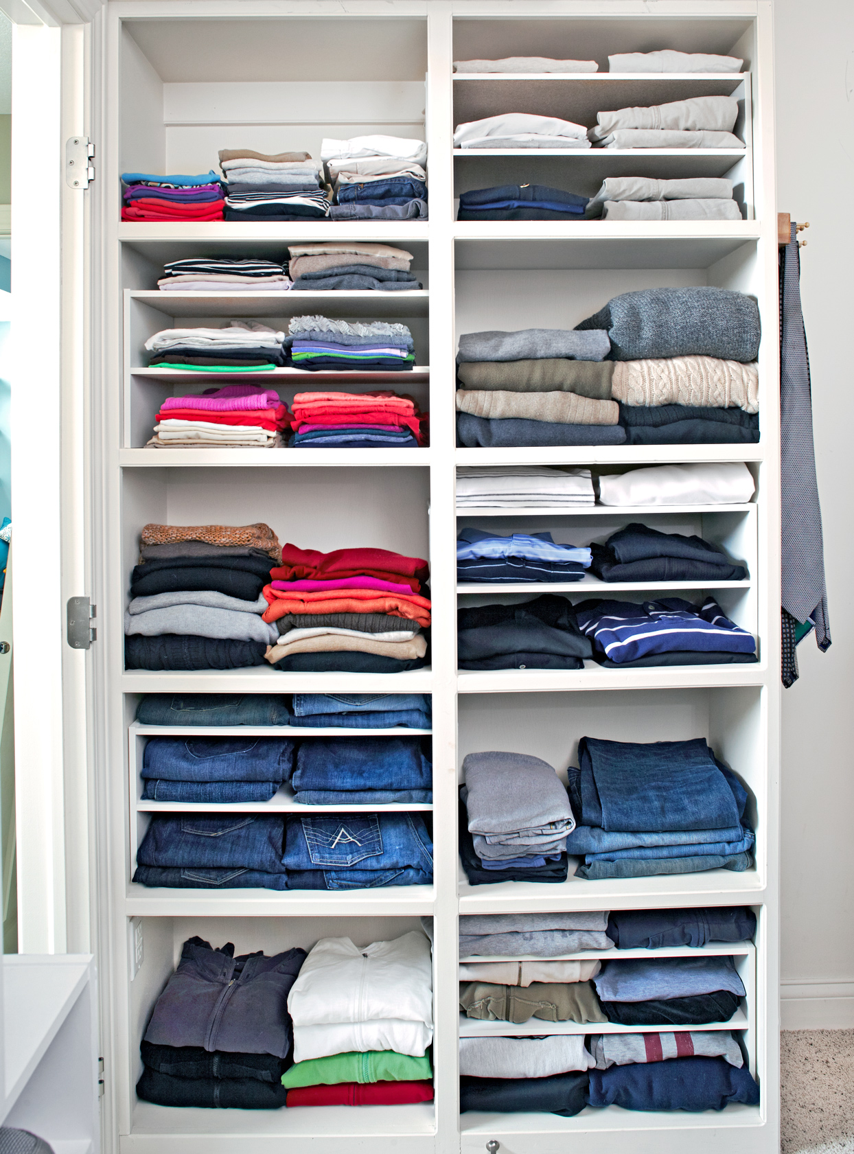 white shelving unit filled with folded clothes