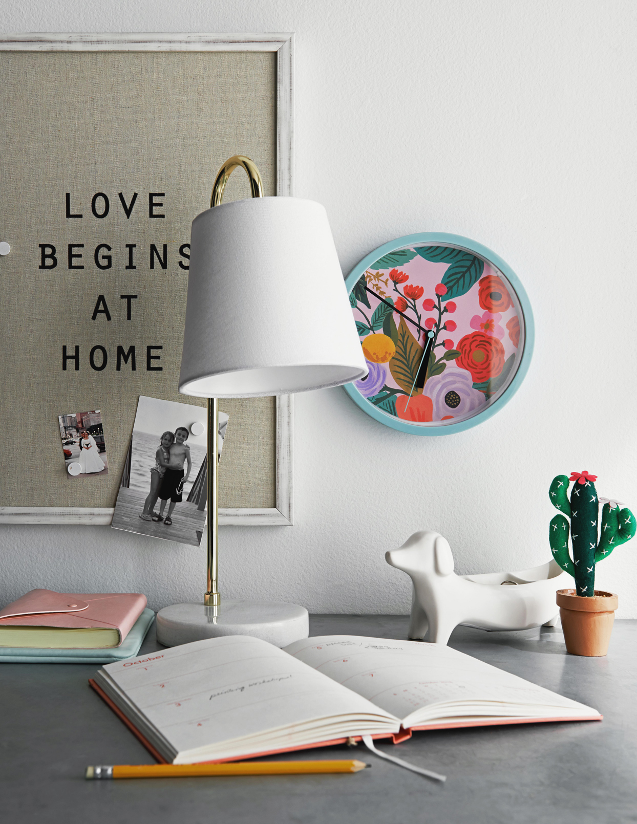 Diary by lamp on table against wall with decor at home