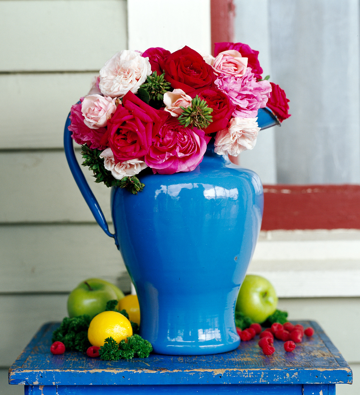 red hued roses arrangement in blue vase