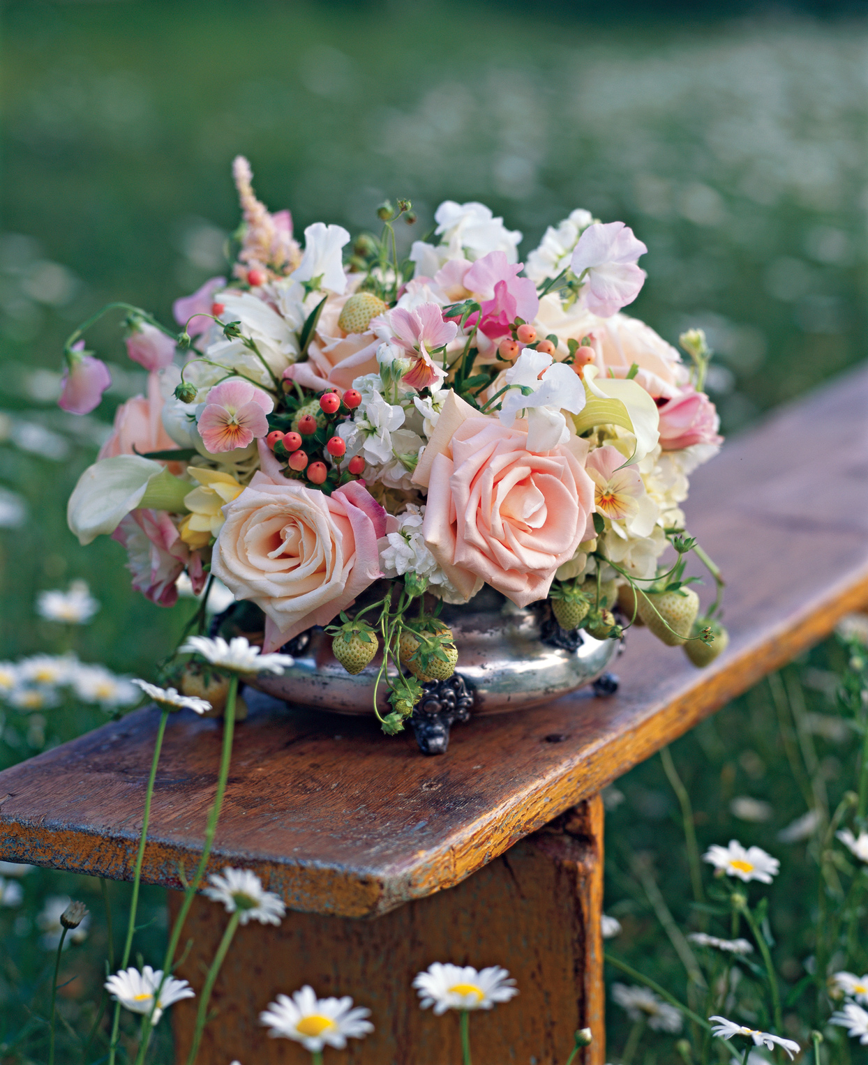yellow pink flower arrangement on wooden bench