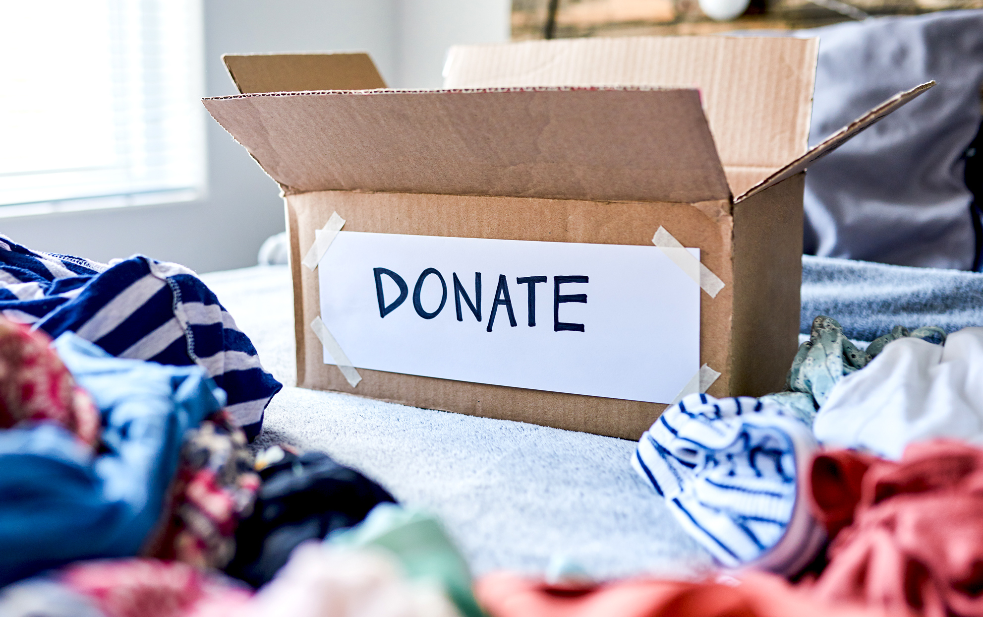 A donation box on a bed with clothes around it