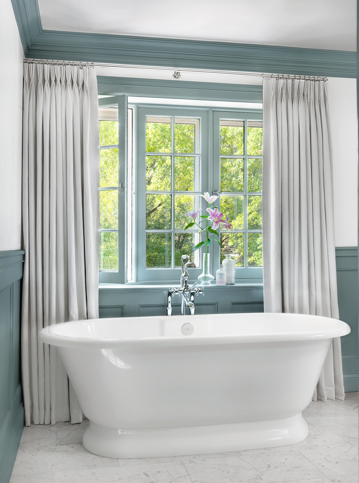 oval blue room master bath tub in front of window