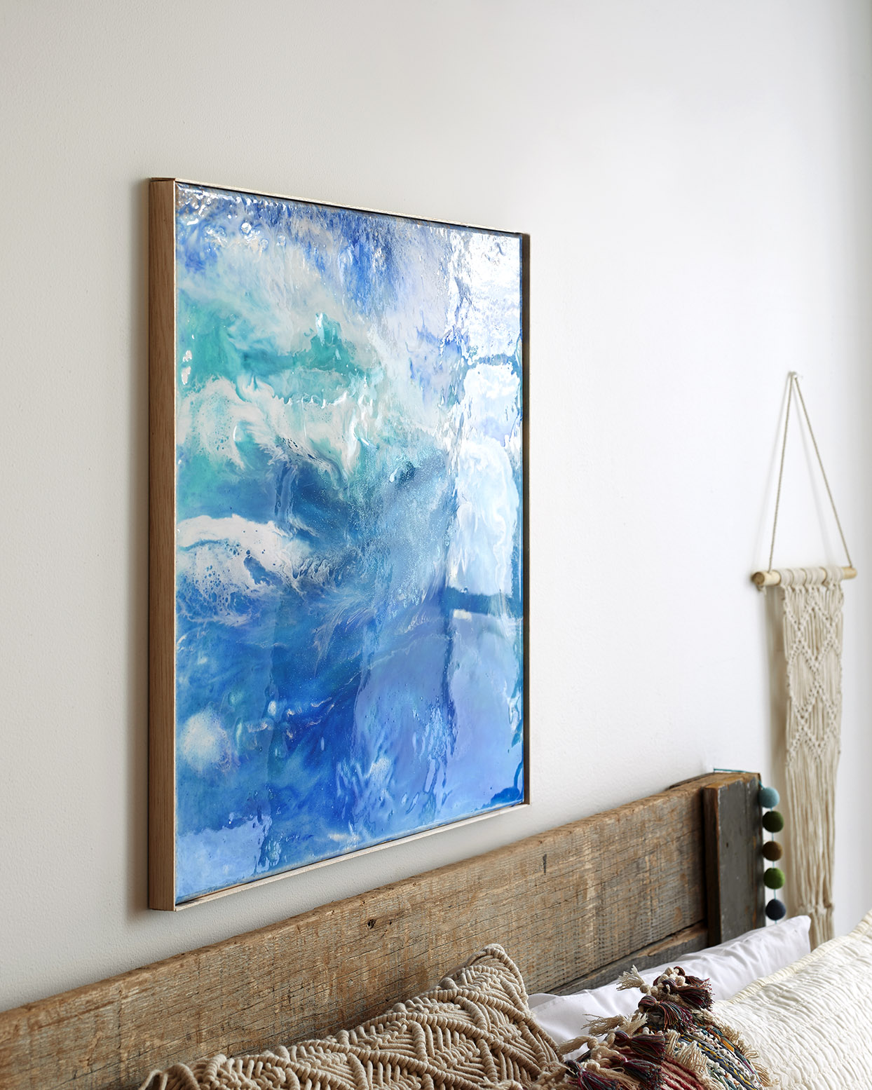blue resin art above a wood bed frame