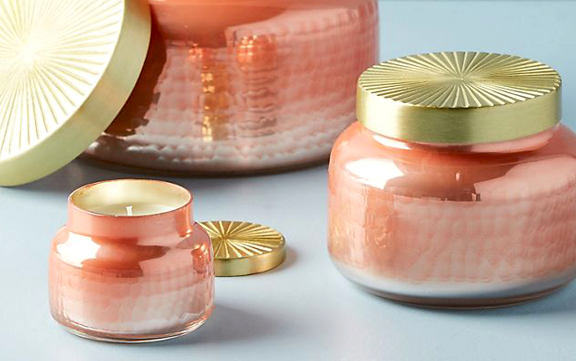 Several pink Anthropologie candles with gold lids