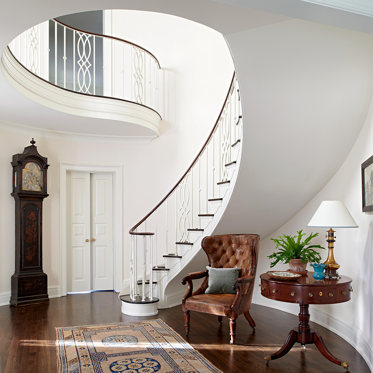 curved white traditional staircase with dark furniture