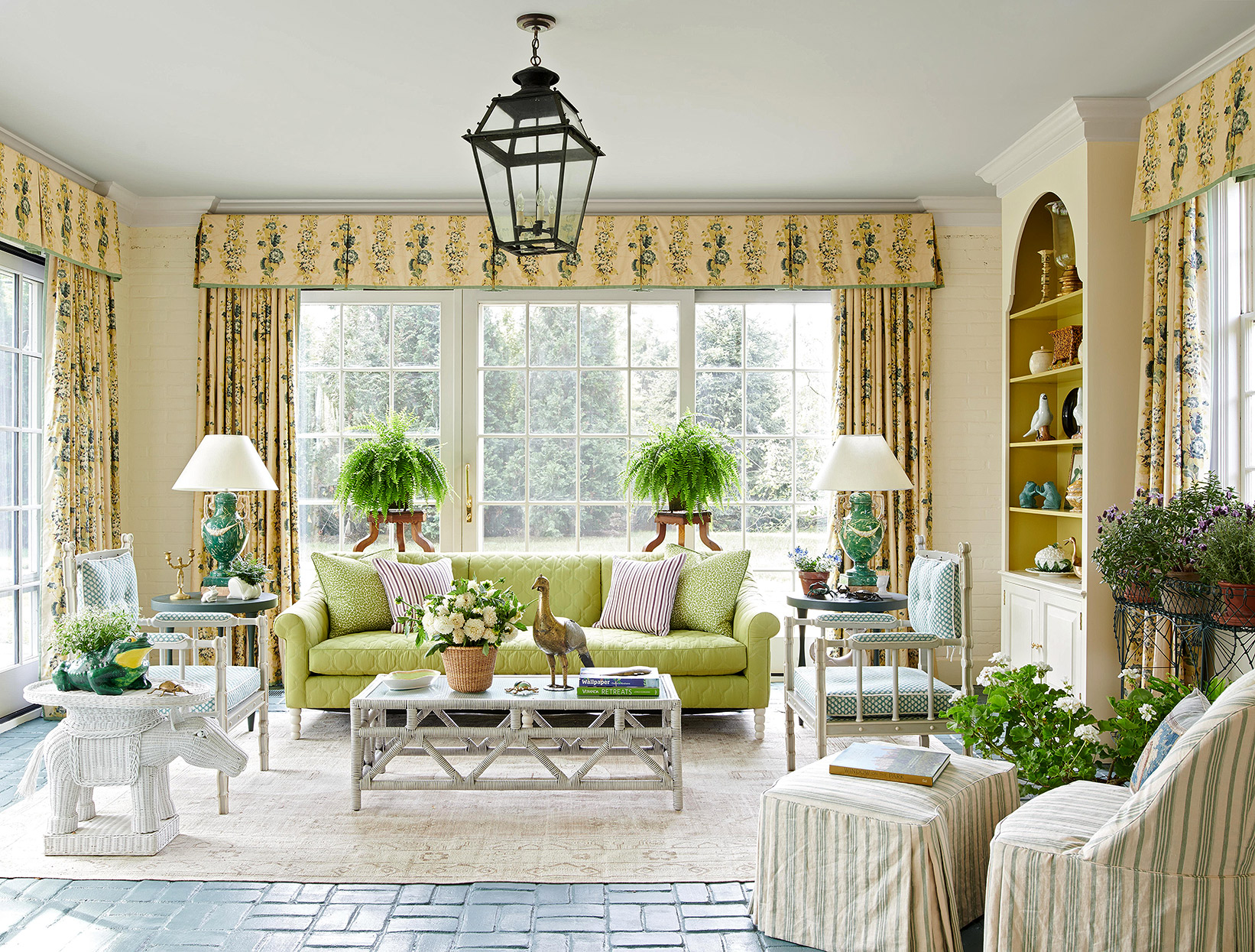 yellow sunroom with bright green sofa and plants