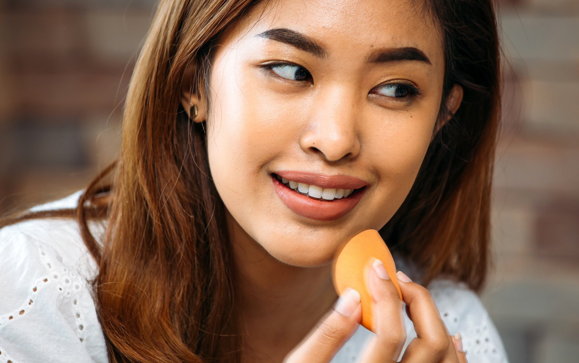 Asian woman applying make up with a foundation sponge