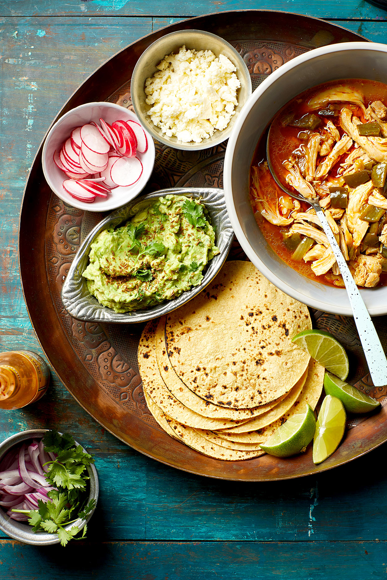Beer-Braised Chicken Tacos with Toasted Cumin Guacamole in pan with tortillas on the side