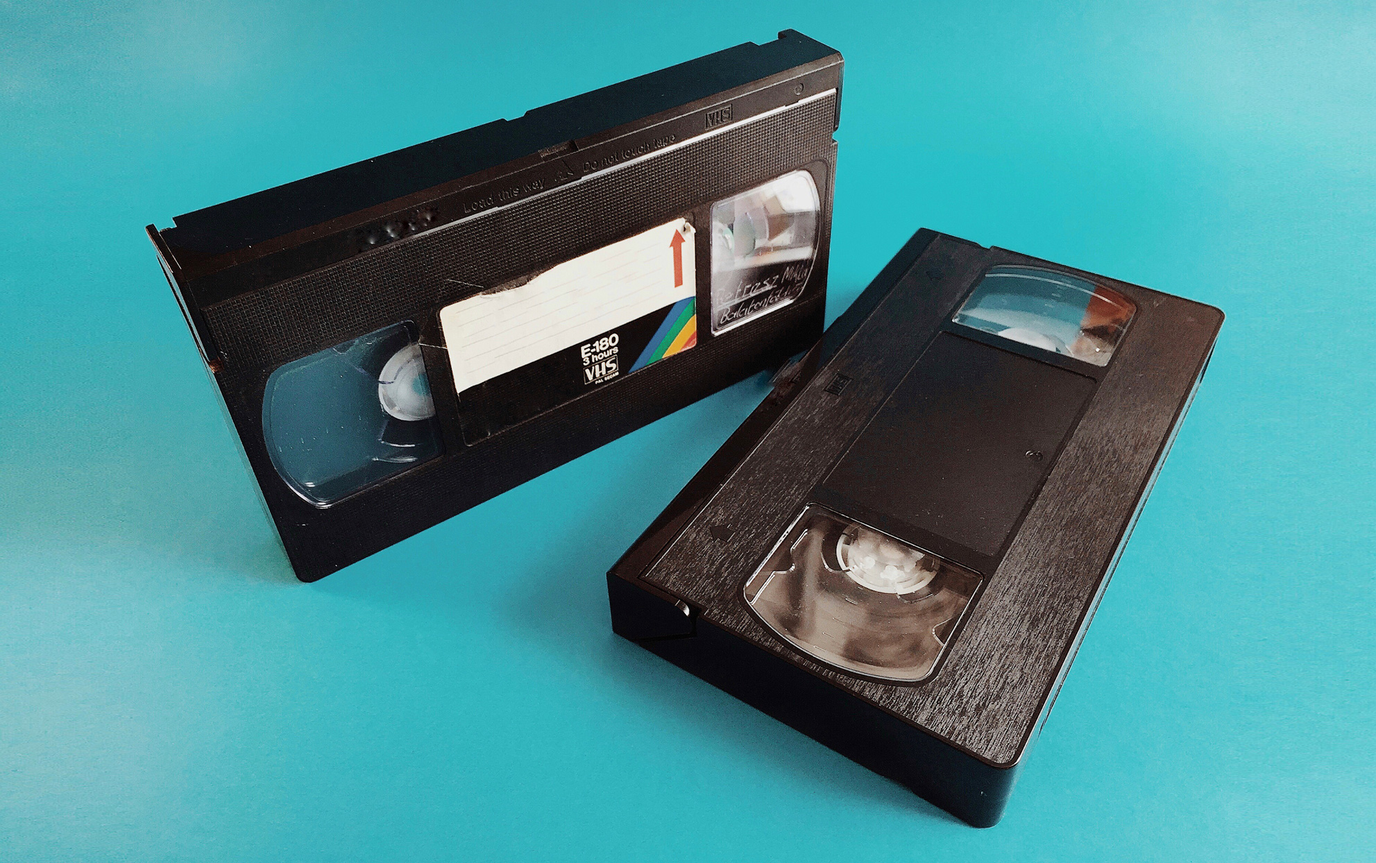 Two VHS tapes on a teal background