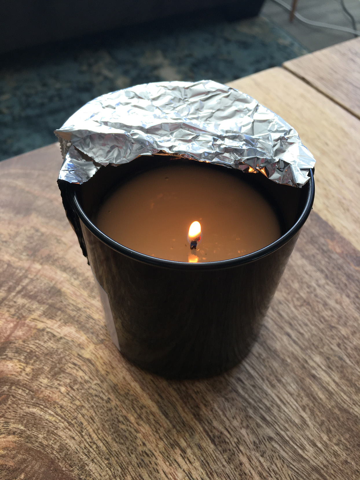 lit candle with foil over edge