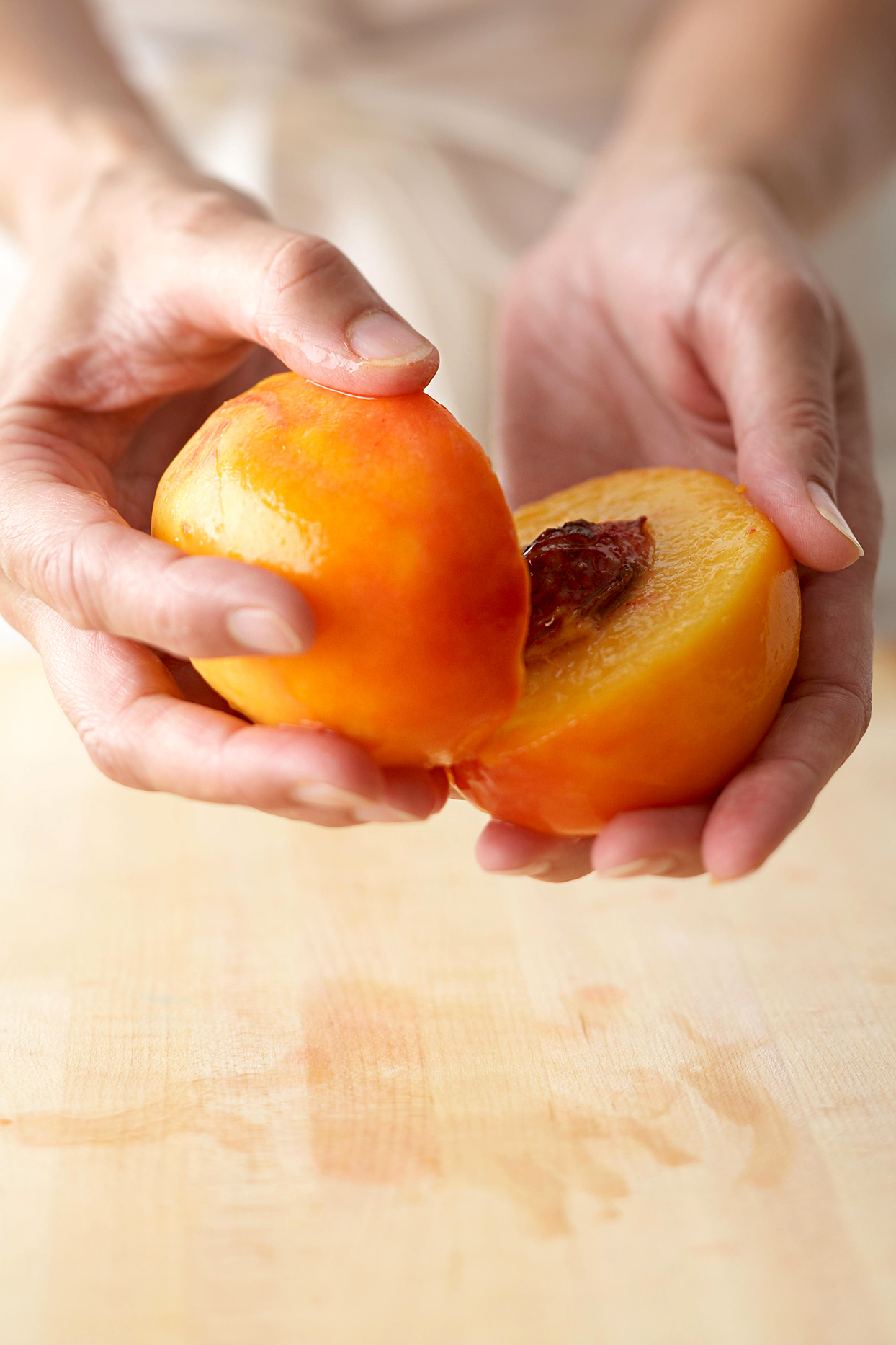 twisting peach to separate into halves