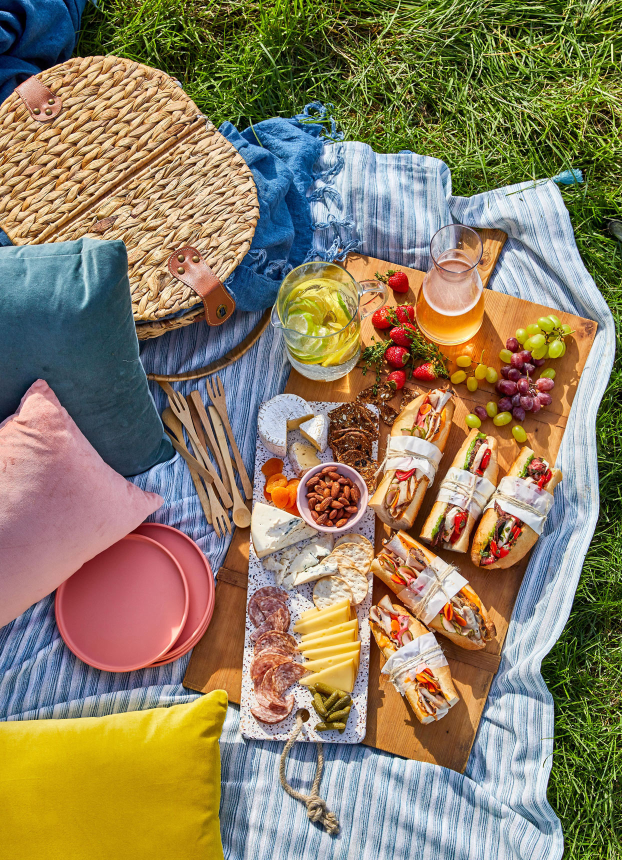 picnic with sandwiches, charcuterie, and pink plates