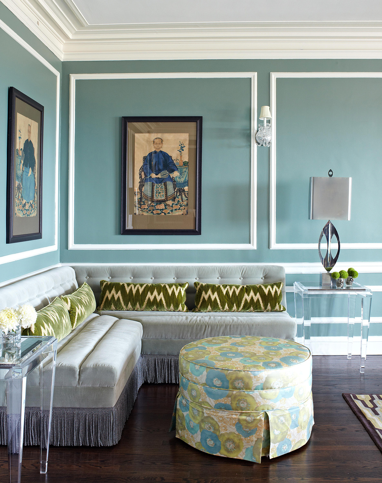 green and blue sitting room with paintings on walls
