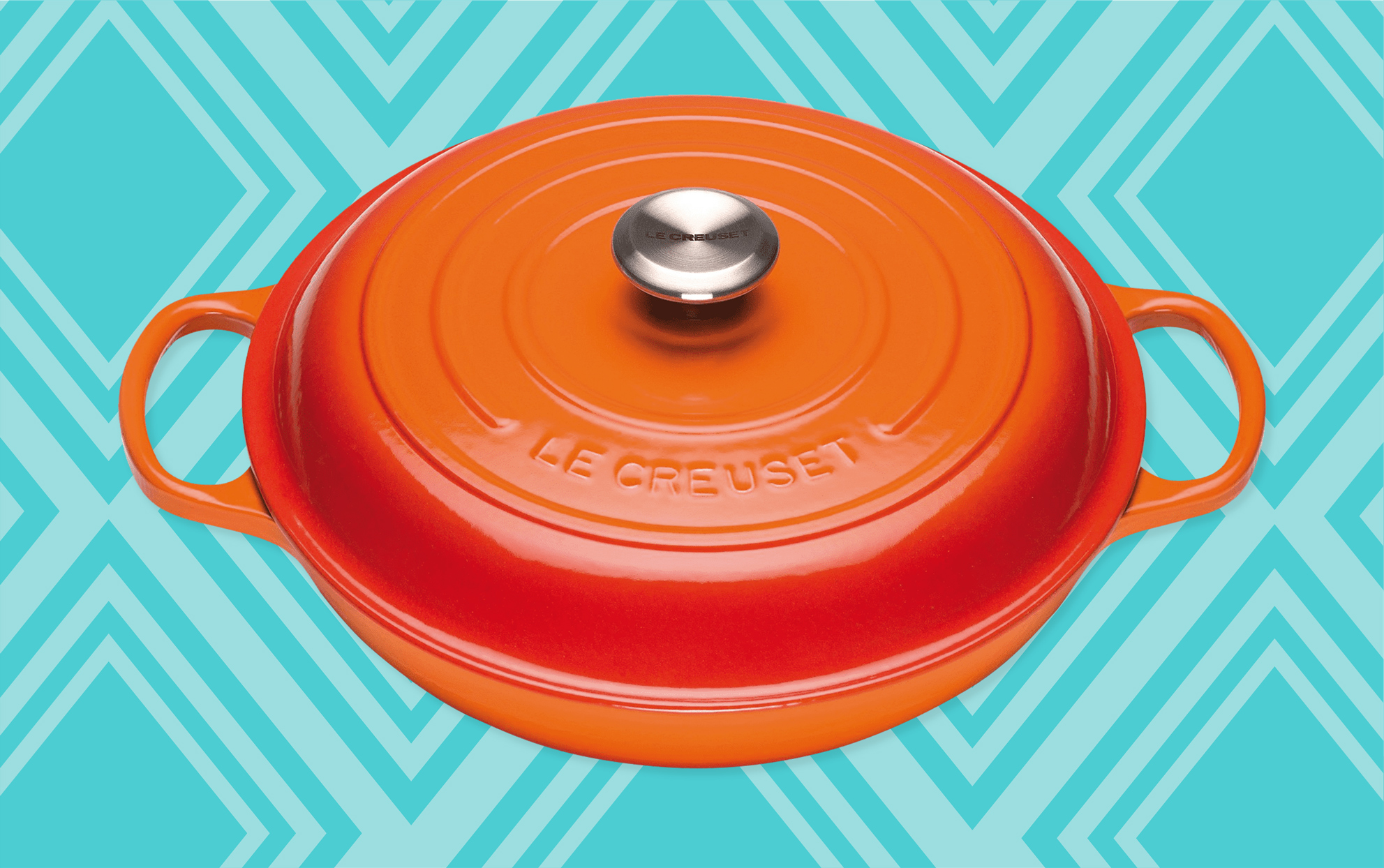 Le Creuset flame colored cast iron braiser on a teal background