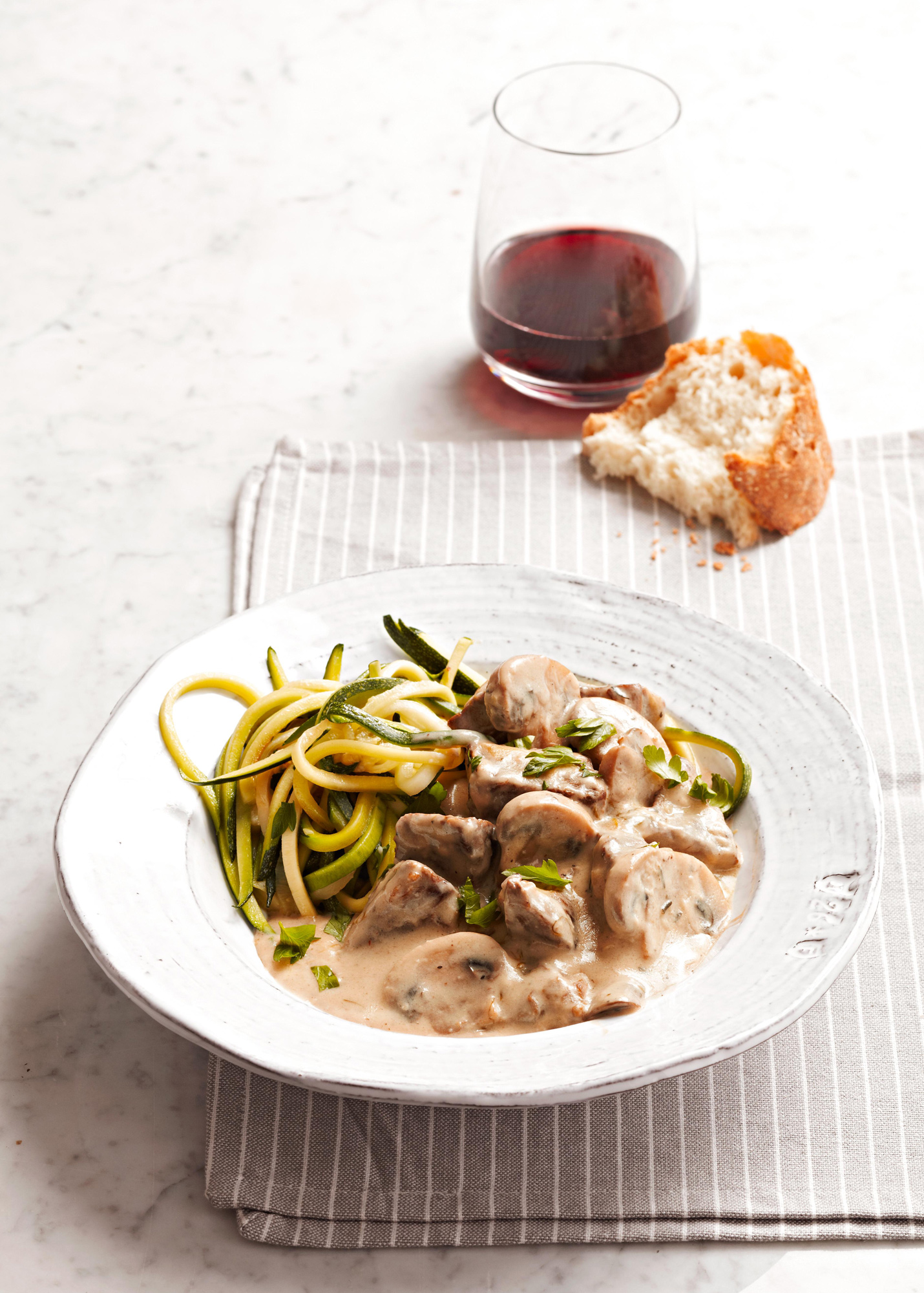 plate of Classic Beef Stroganoff with side of bread and glass of wine