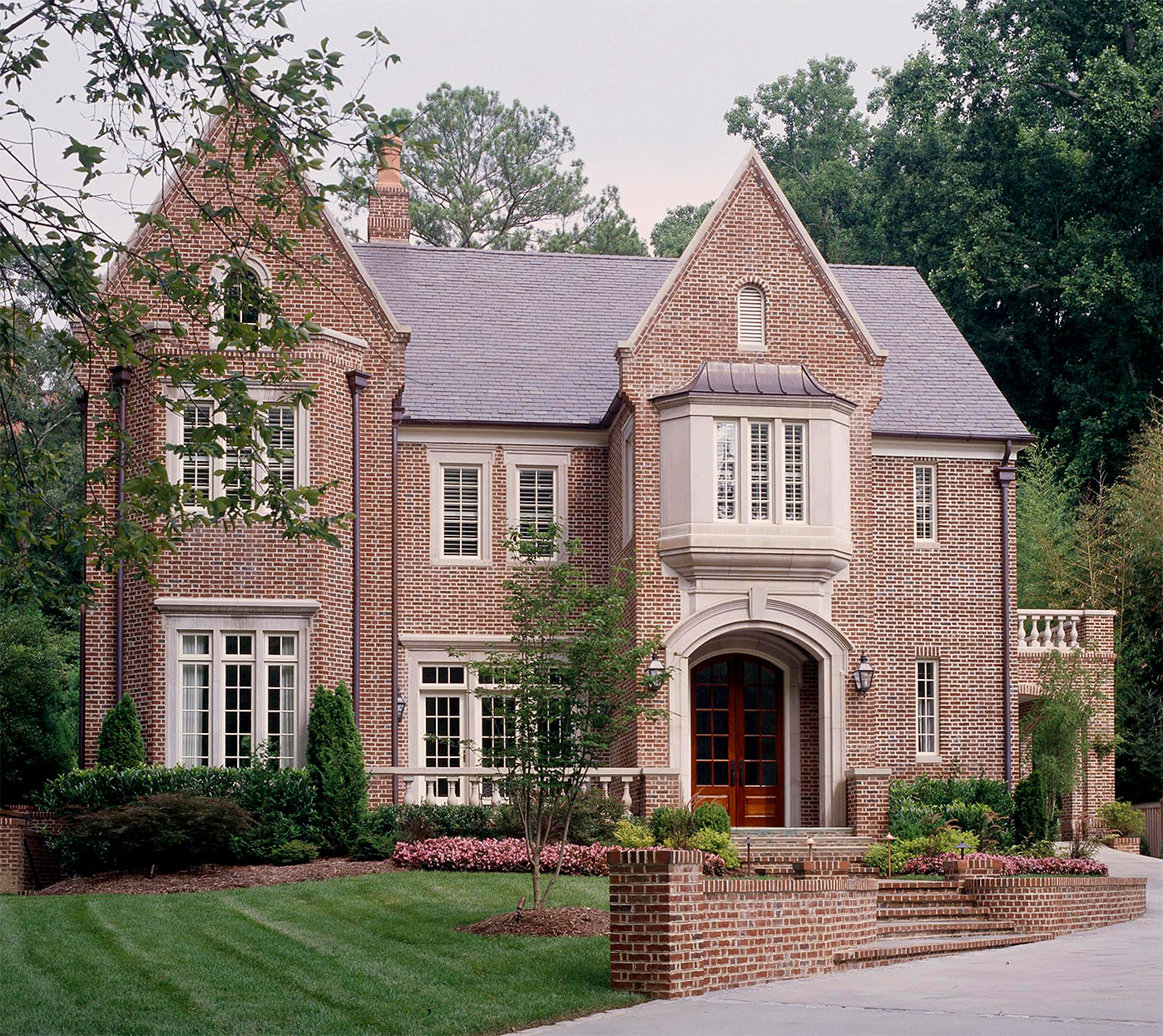 brick tudor home with grouped windows and transoms
