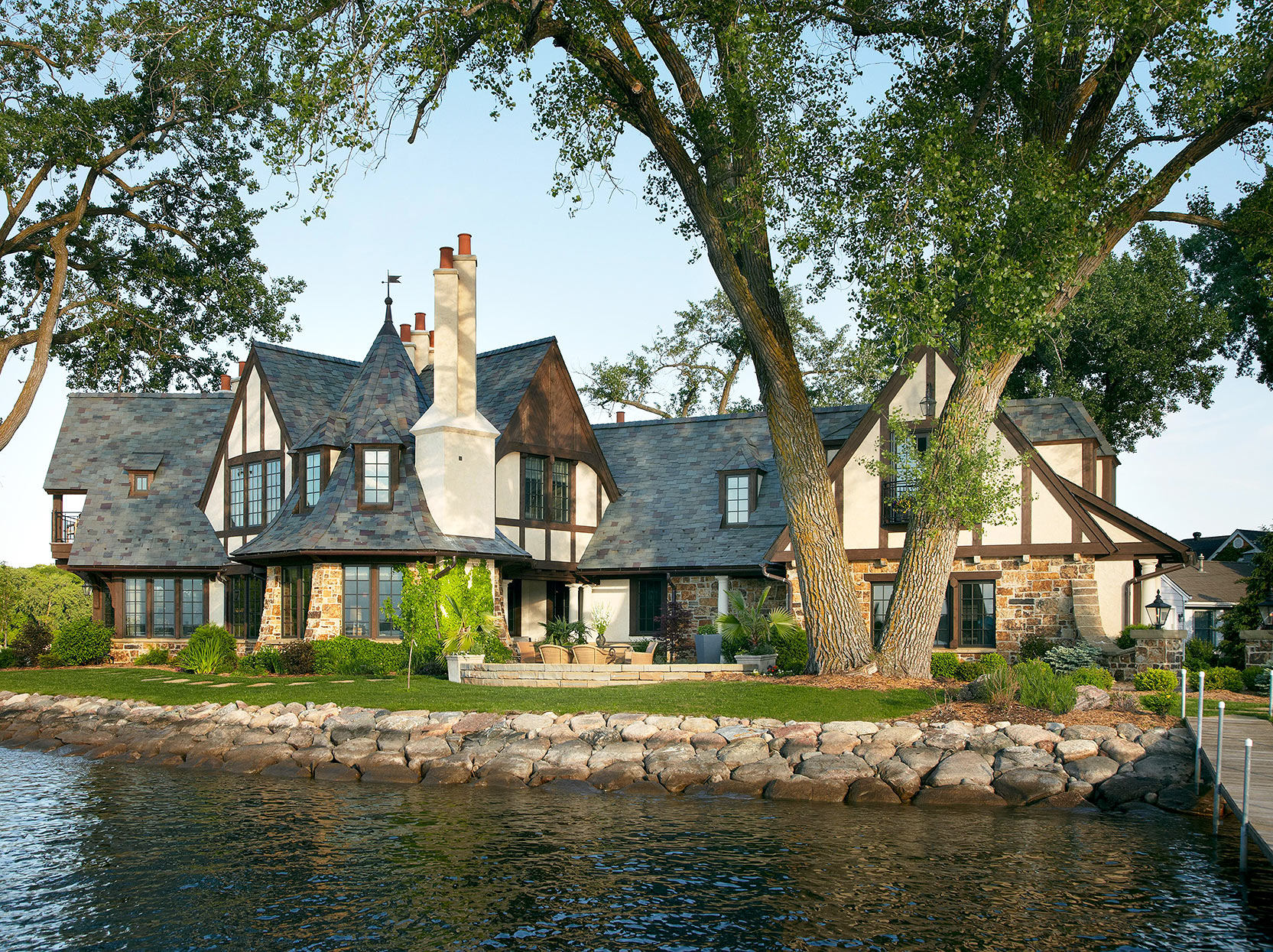 lakeside tudor with slate-tile roof and offset chimneys