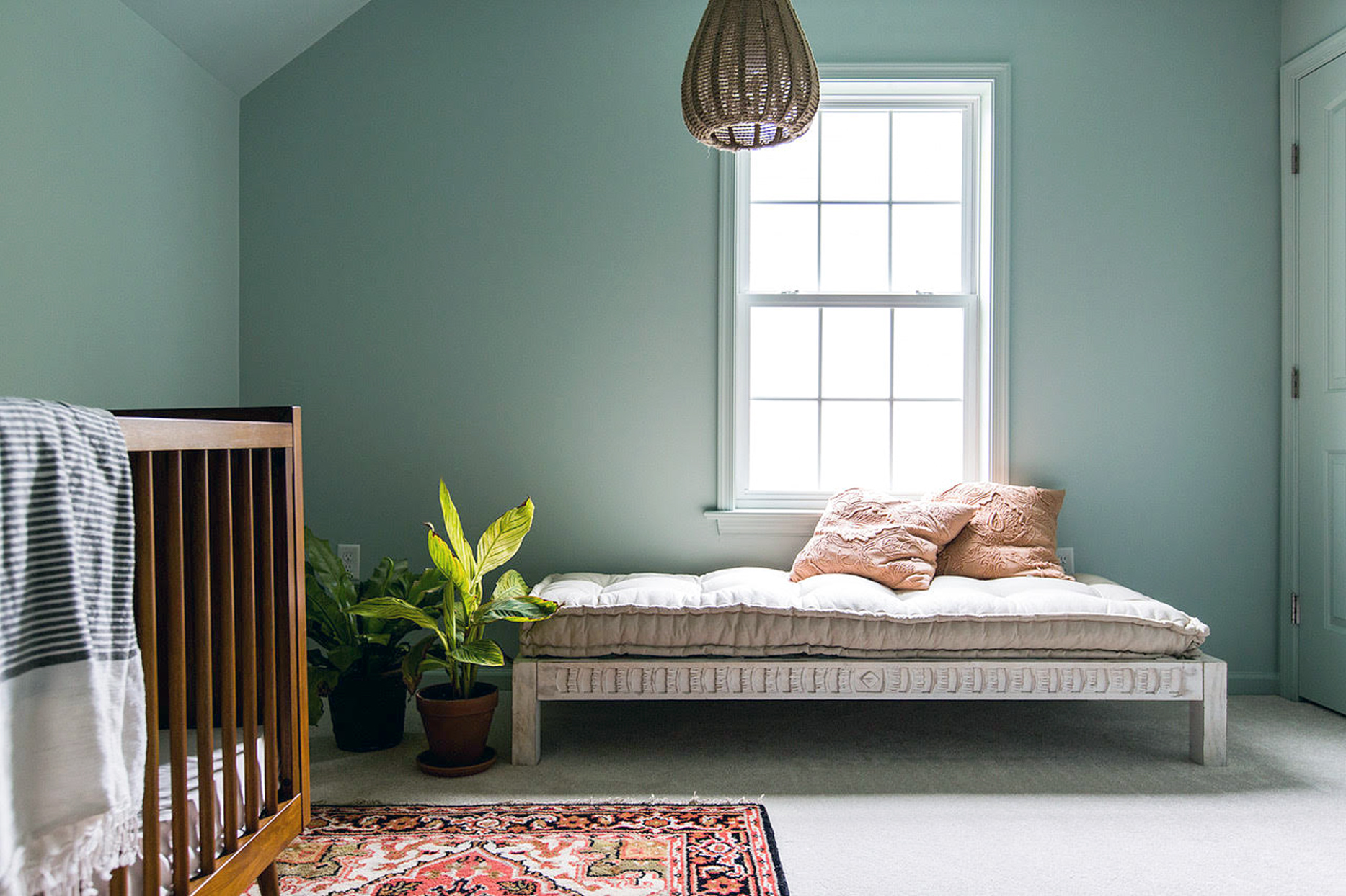 teal room with daybed and crib