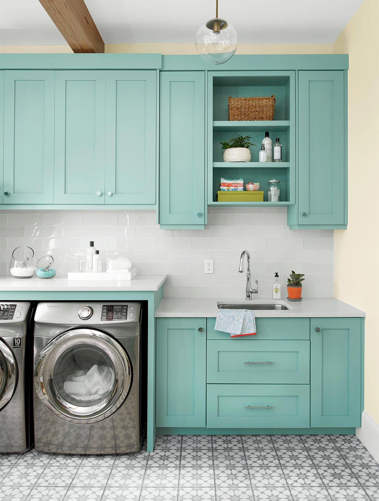 laundry room with modern tile and mint-green shaker cabinets