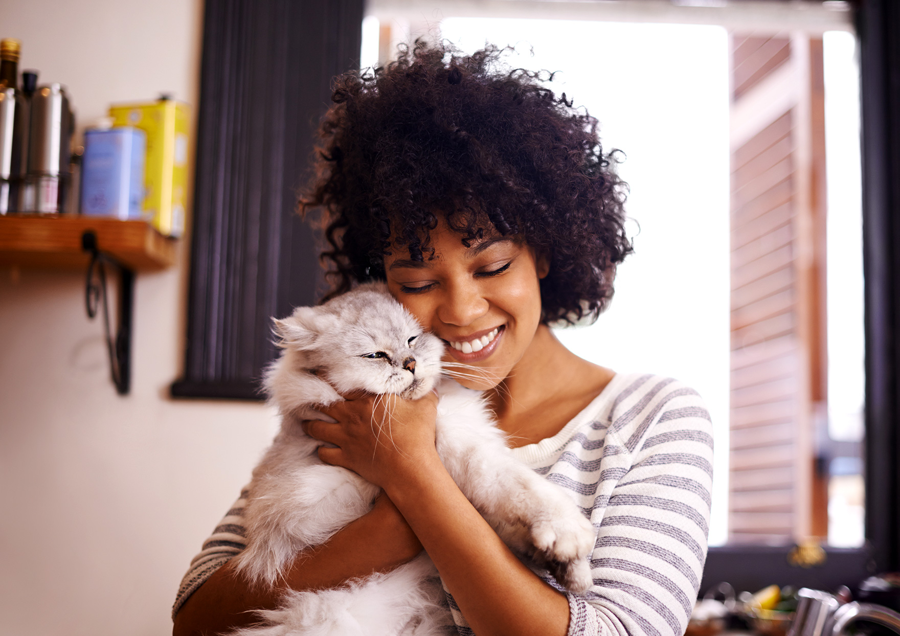 woman smiling and holding cat