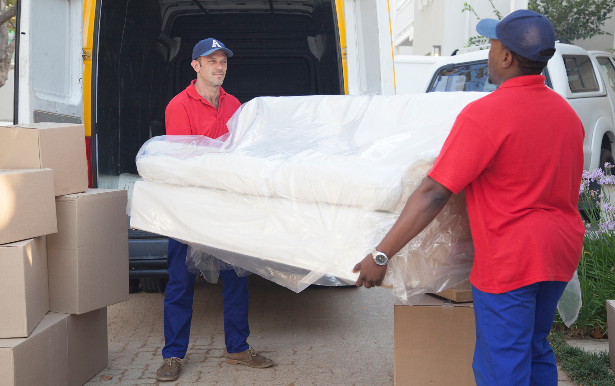Two men delivering a white sofa