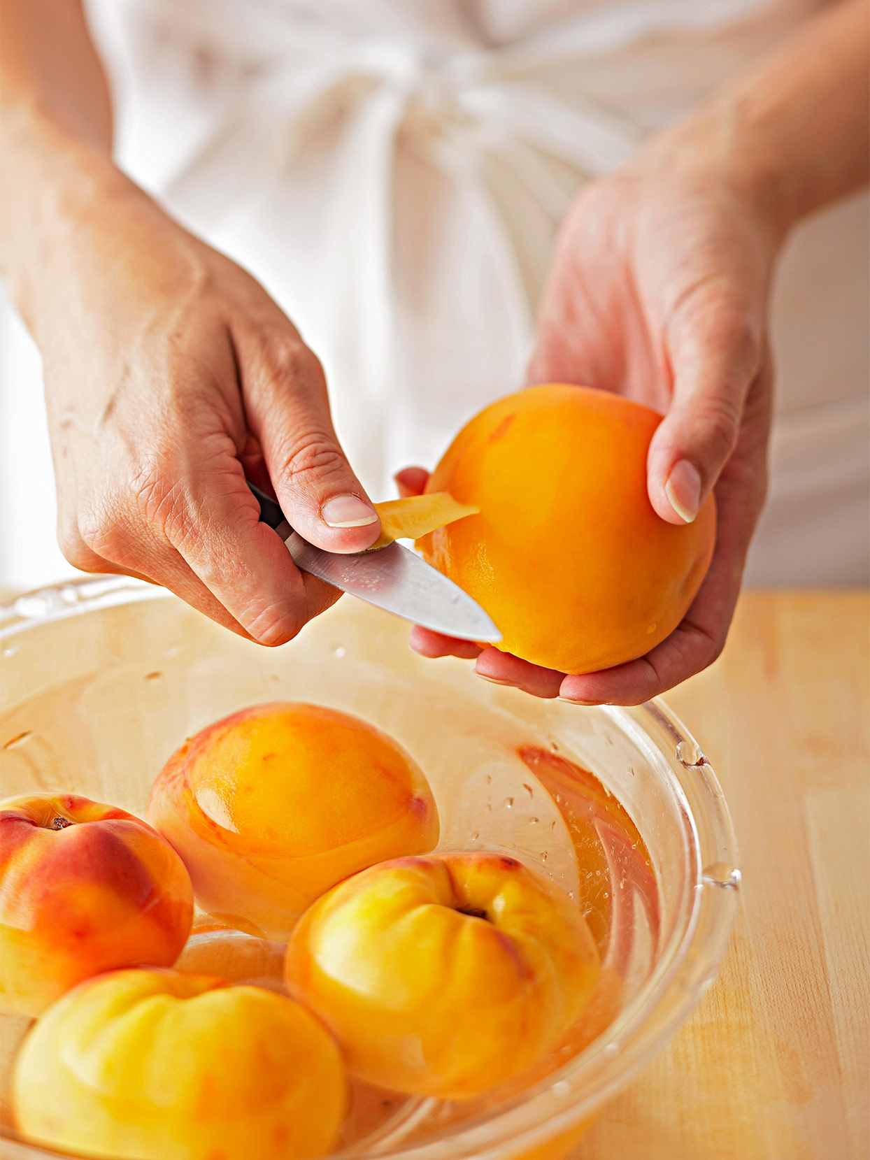 peeling peaches above bowl of water
