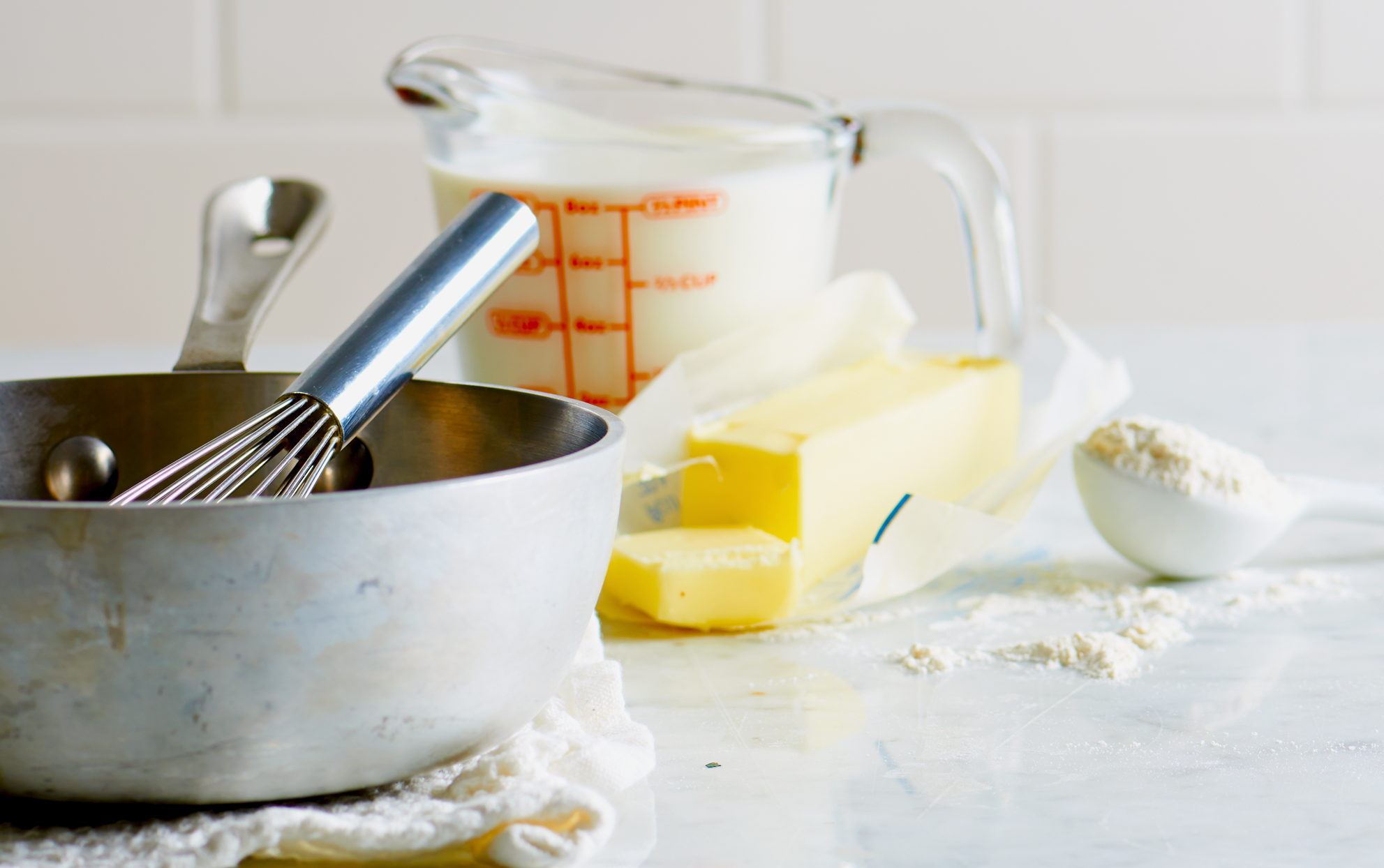 sauce pan, butter, flour and milk on a kitchen counter