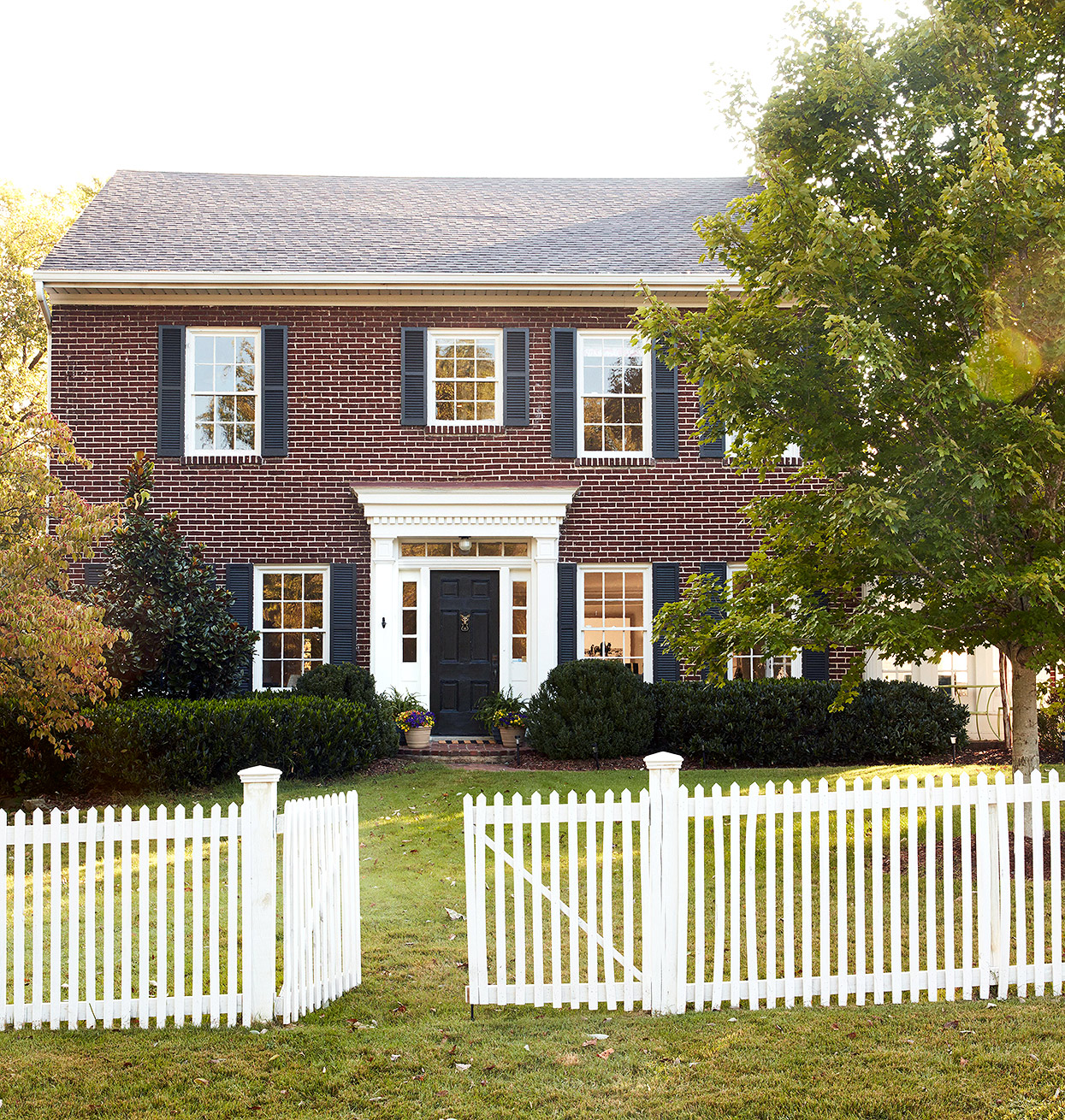 brick colonial home exterior with white picket fence