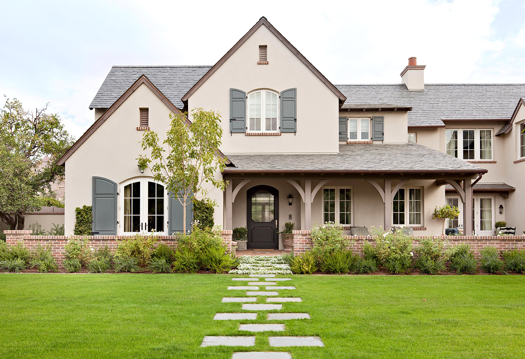 stucco exterior with gray shutters and pavers to door