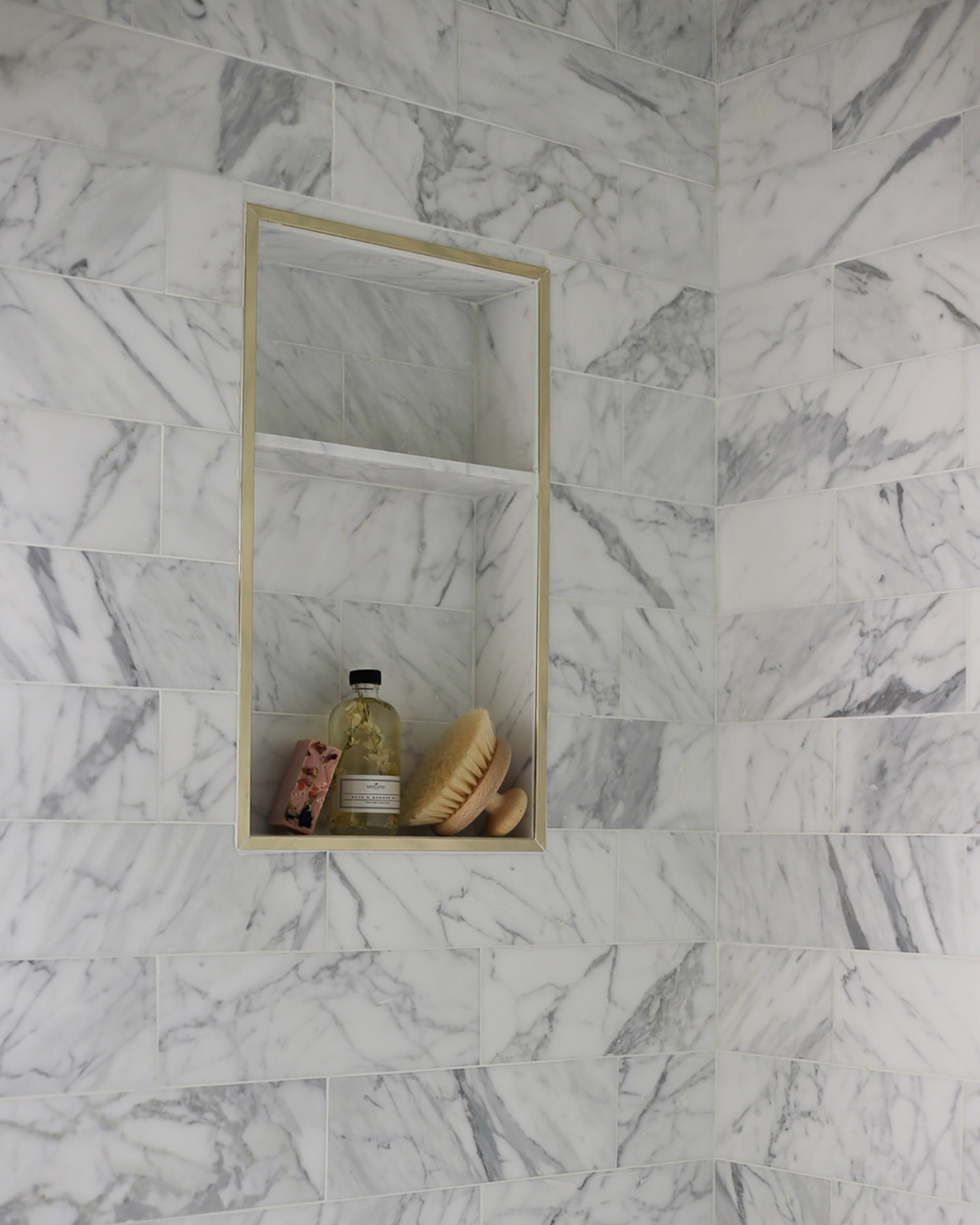 white marble tiled shower with wall niche