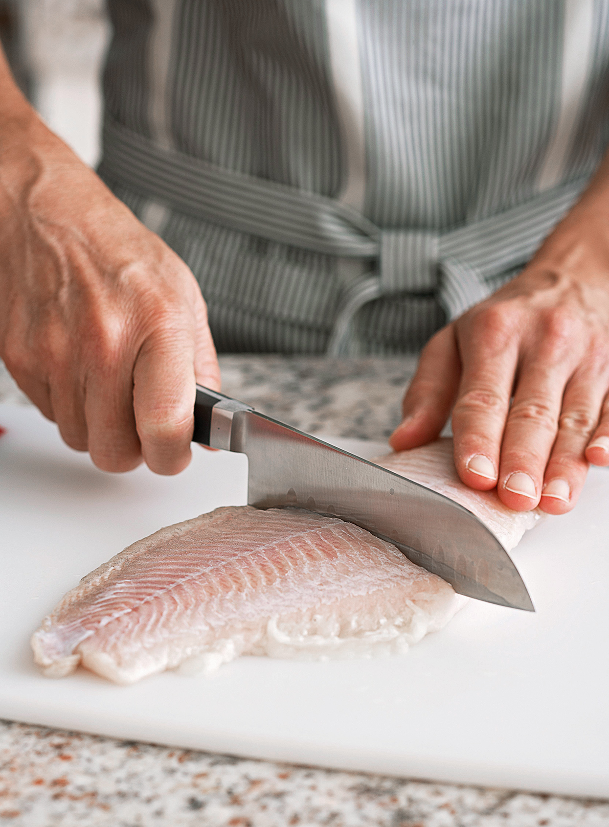 cutting fish fillet with knife on cutting board