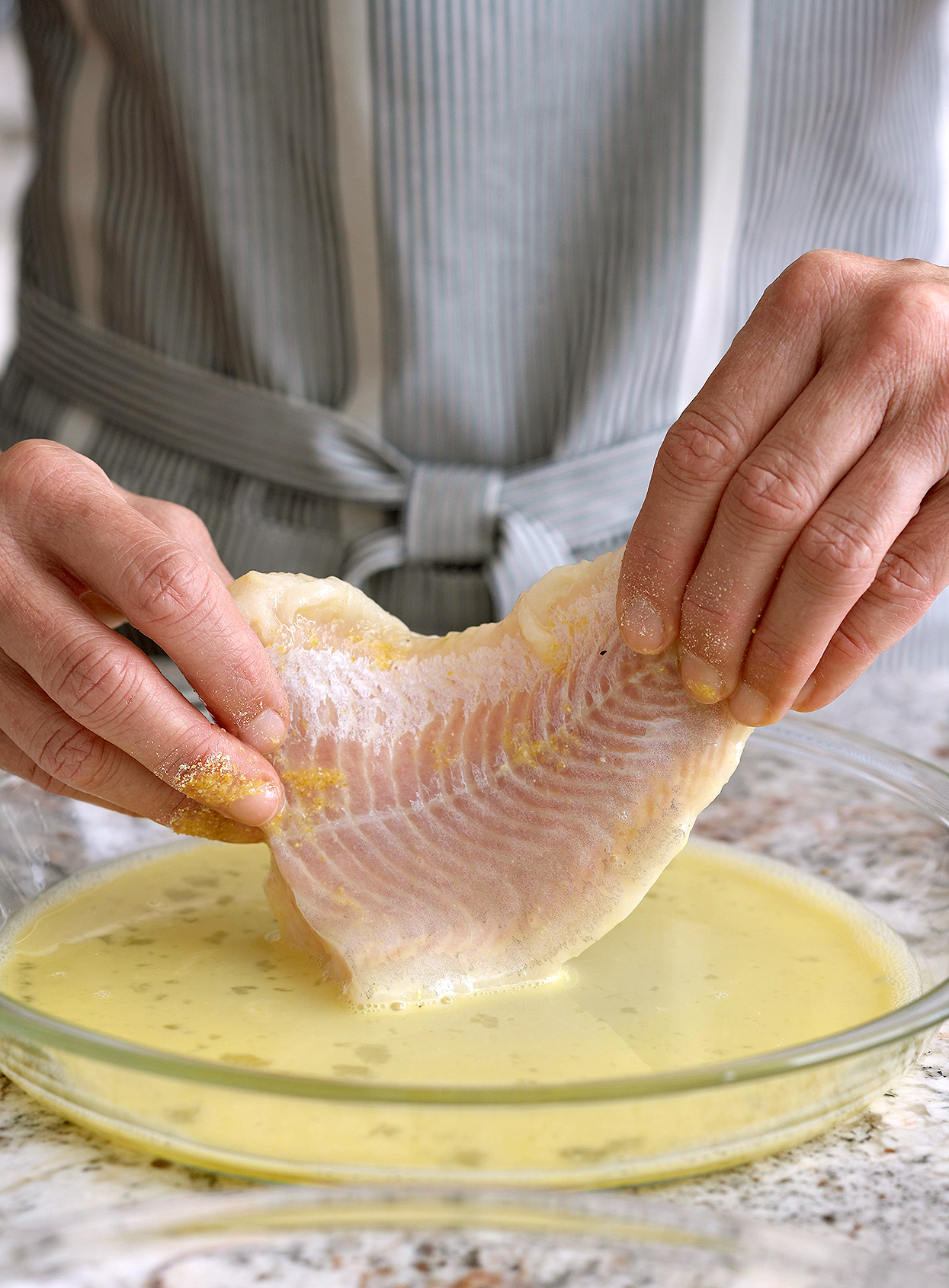 dipping fish fillet in egg mixture to coat