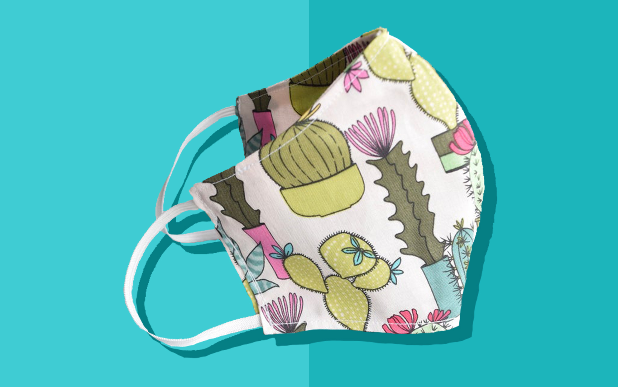 Stylish face mask made out of printed succulents material on a teal background