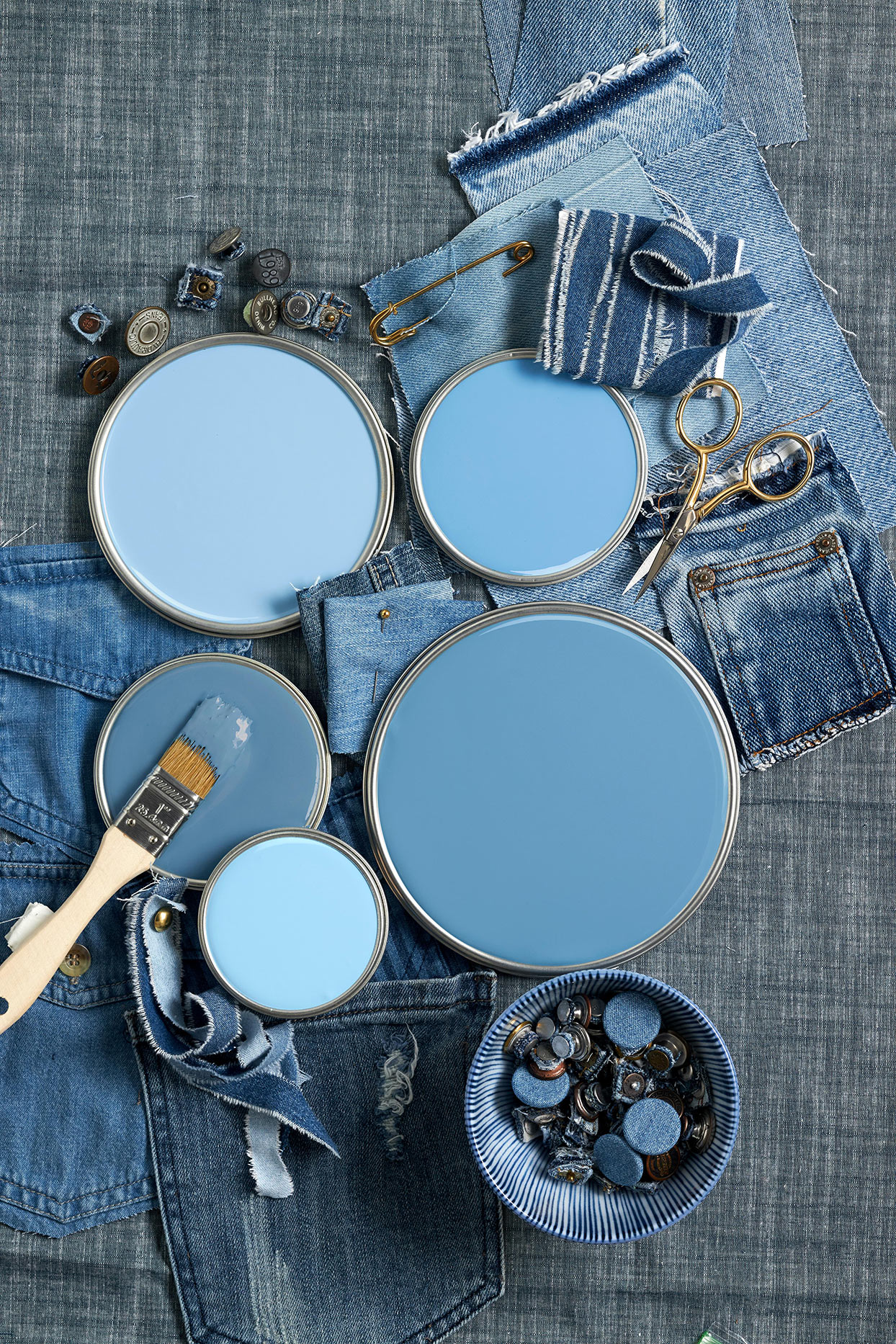 Blue paint lids on top of denim