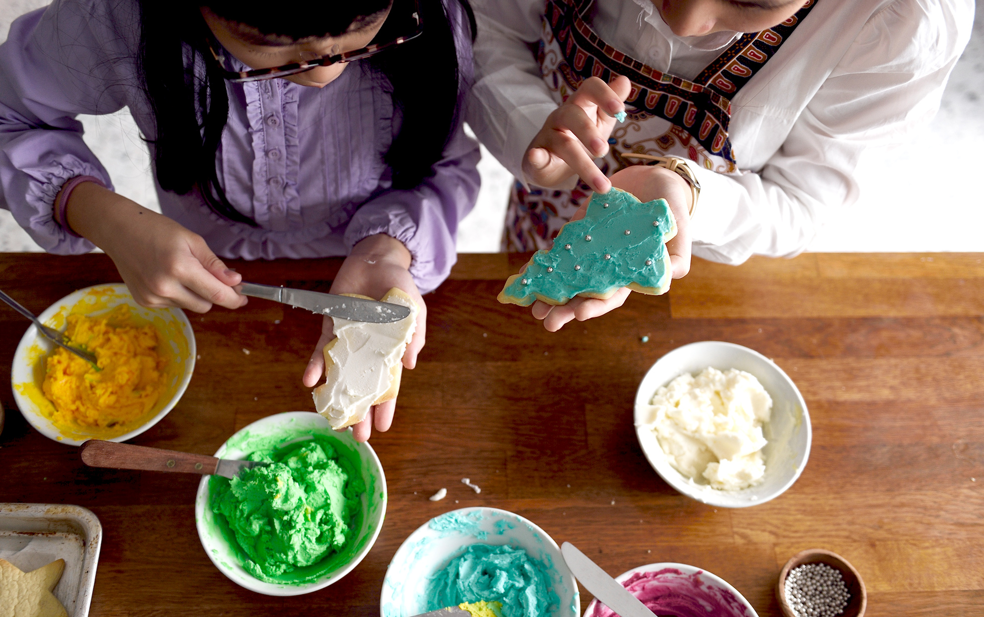 Two girls decorating holiday cookies at a table