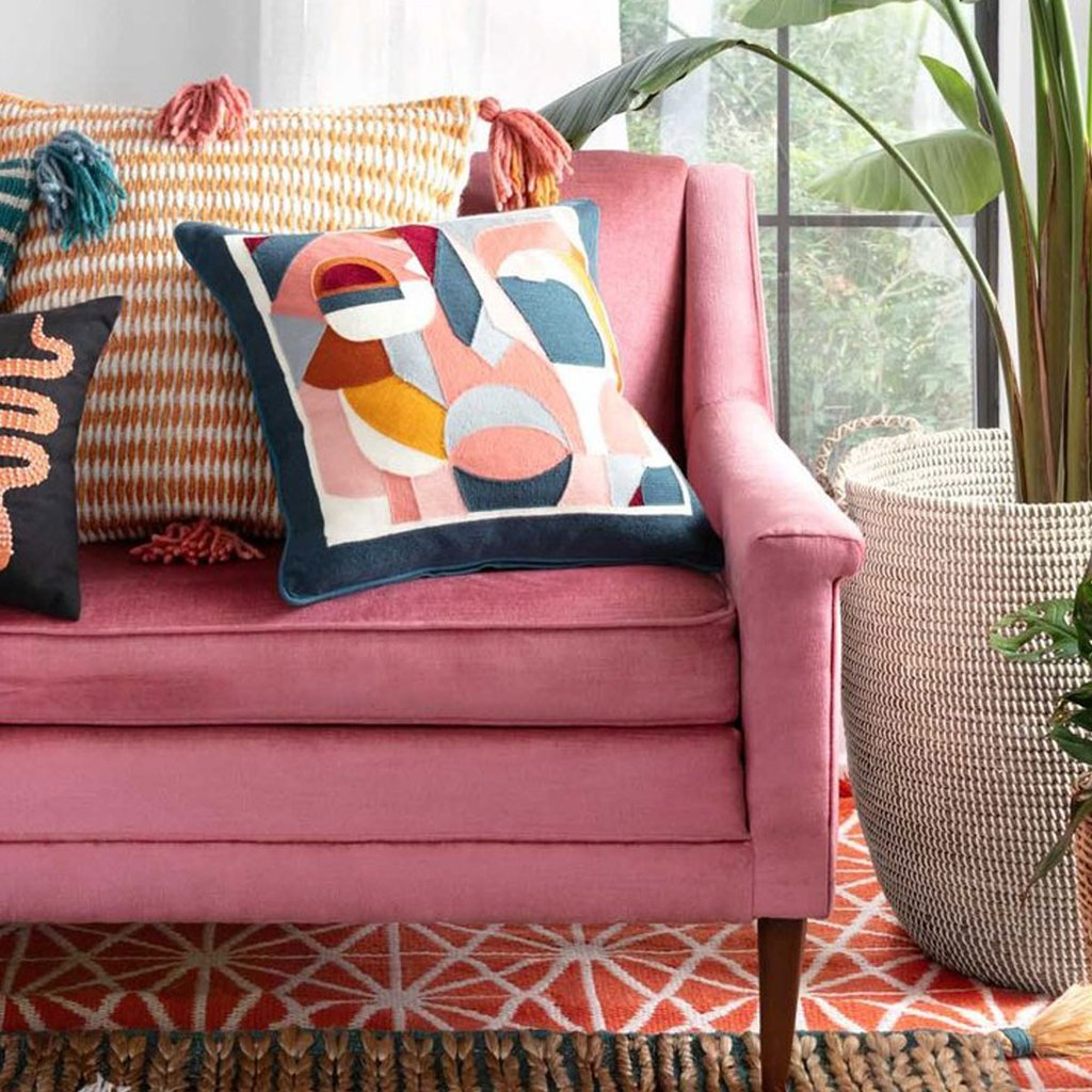 colorful throw pillows on a pink couch