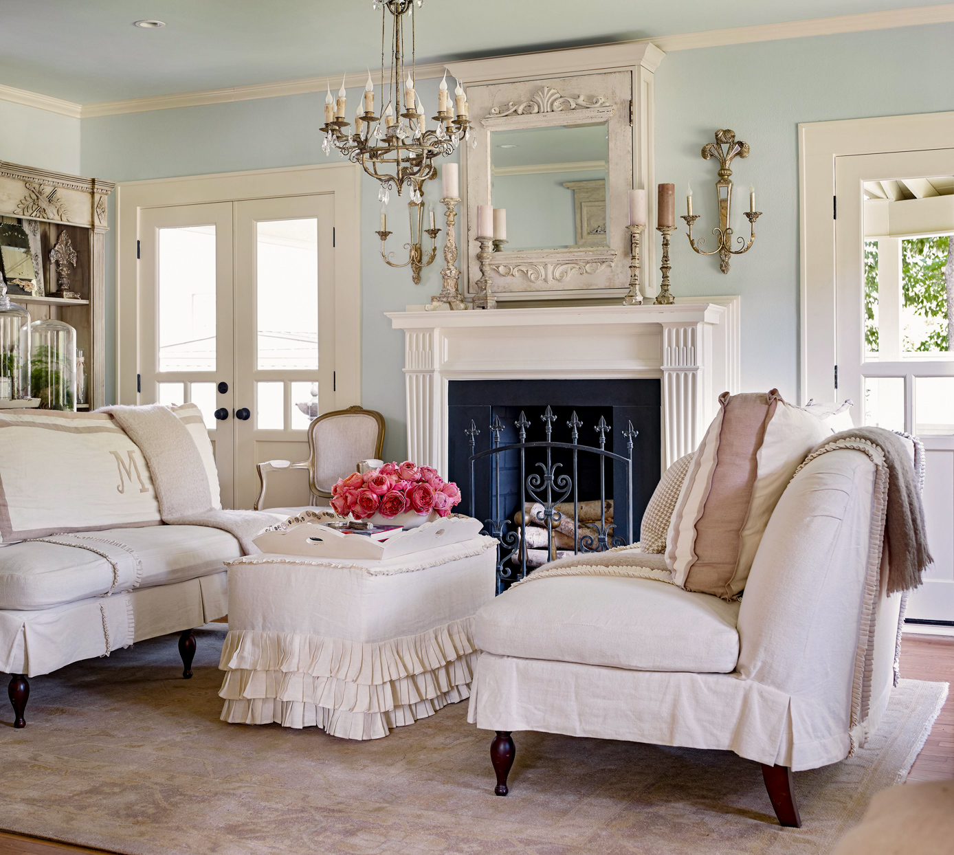 sitting room with elegant chandelier and wall sconces