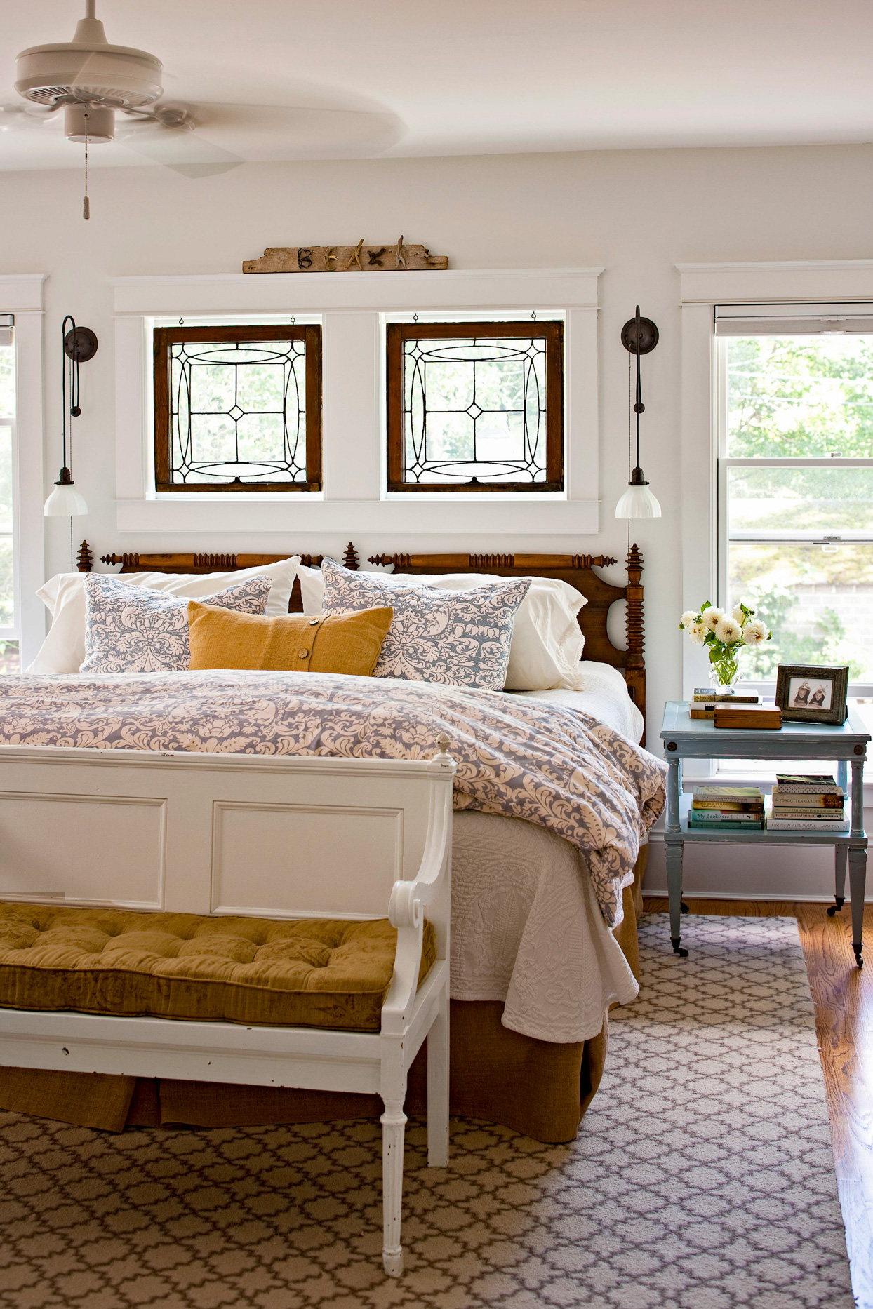 white bedroom with dark wood headboard and yellow accents